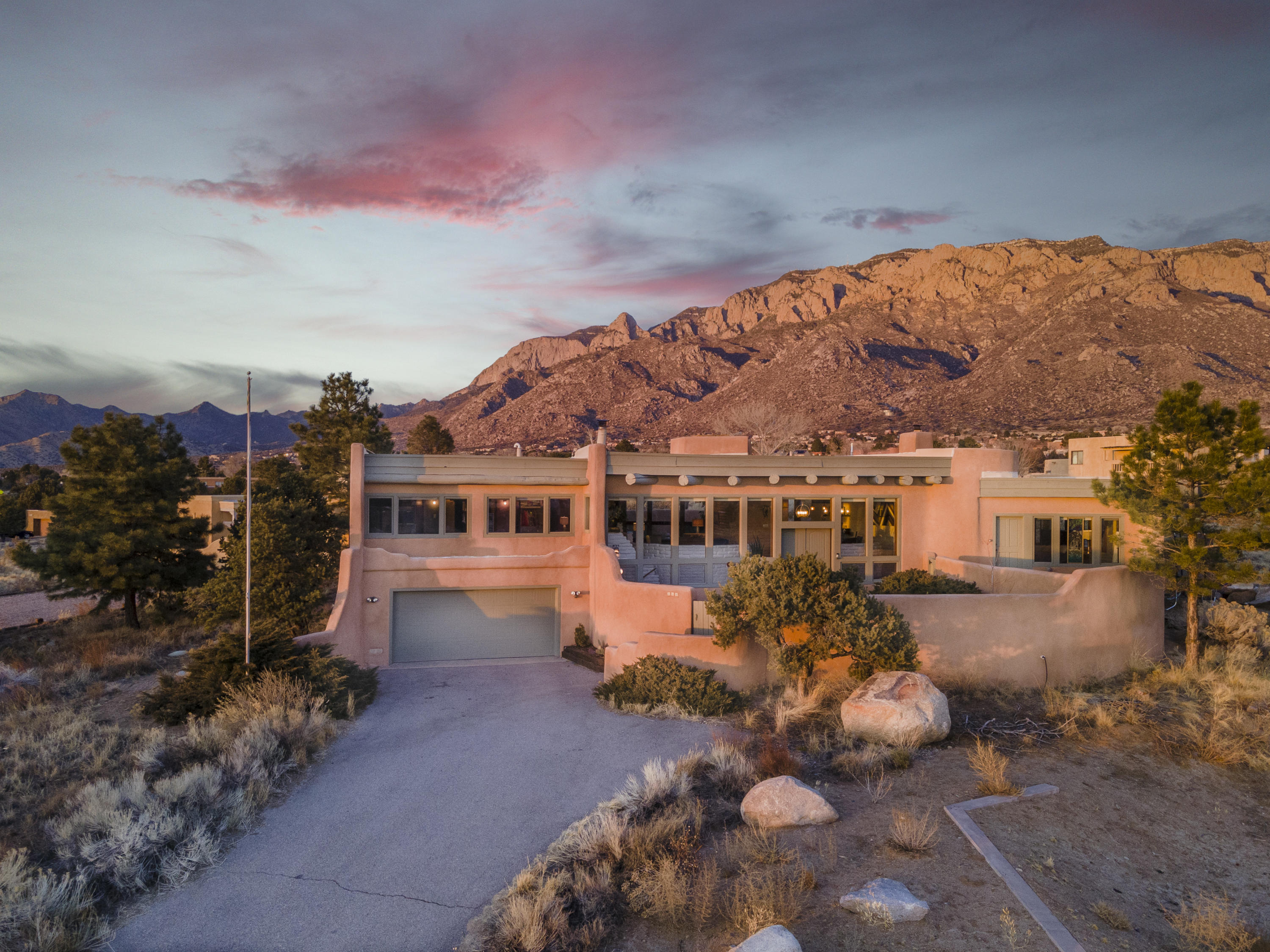 . Absolutely stunning Custom Adobe Sandia Heights Home built by Roybal situated on an elevated incredible lot (0.61 acres) that takes full advantage of the VIEWS of the Sandias, so close that you feel as though you can touch them. Versatile open floorplan offering 3 bedrooms and an office/study, and two baths which have been updated (2019&2020). Wood windows, Kiva fireplaces, brick flooring, newer carpet, tile, lightning & paint throughout. GORGEOUS Kitchen, which has been totally remodeled (2018) to include new cabinets, backsplash, stove, microwave, granite countertops, and bar that opens to the eating area. Spacious Owner's Suite with its own Kiva fireplace, private entrance to the large deck with stunning Views of the City & Sandias.