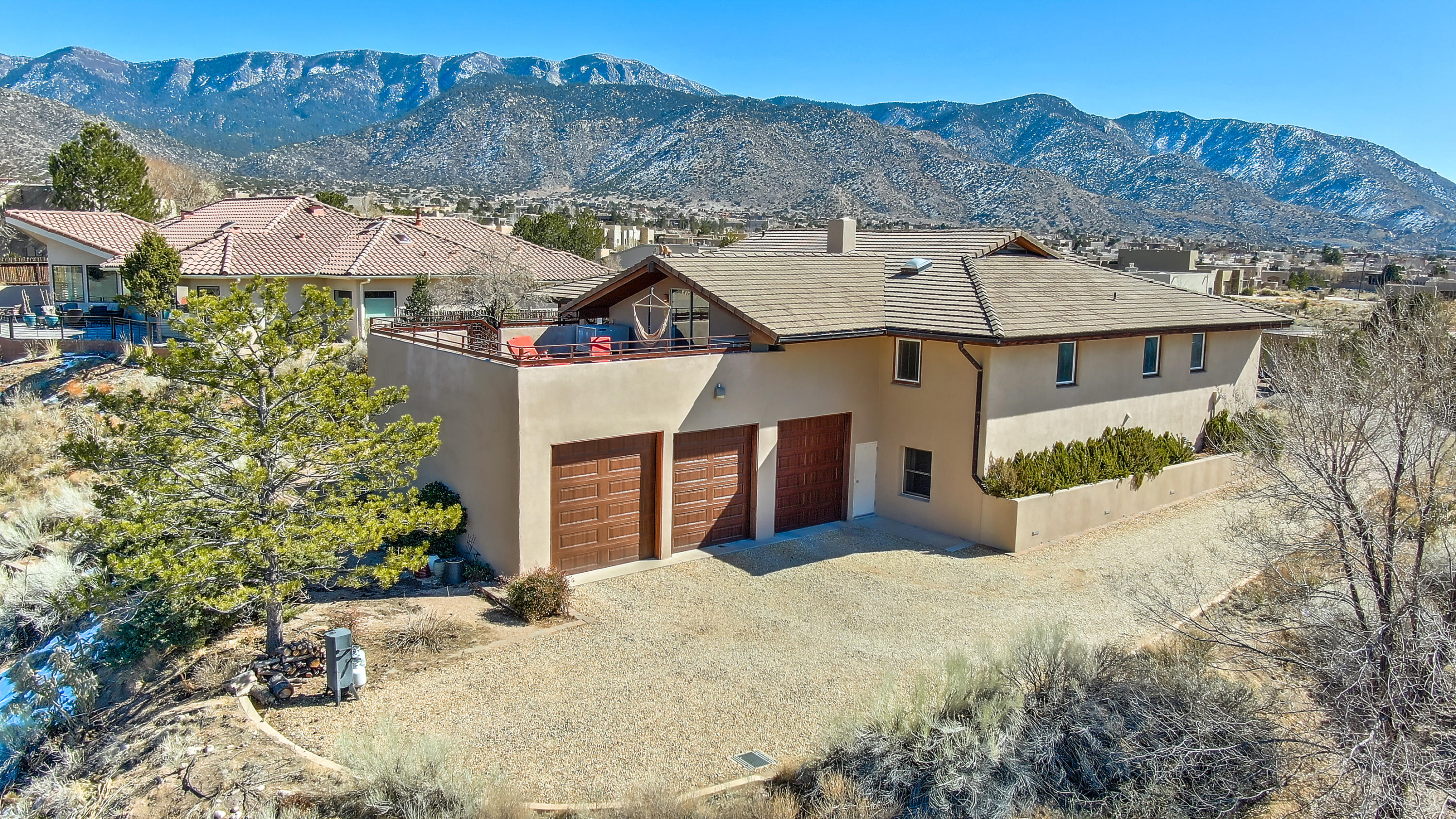 Striking estate on an elevated 1.6 acres, abutting Pino Arroyo w/wild life & magnificent views of the city & the Sandias! Elegant, octagon shaped living room is the heart of the home, a place for gatherings or snuggling by the impressive fireplace. Grazing is welcome around the kitchen island, breakfast in the banco and you'll love those casual summer evening soiree's w/majestic sunsets from the upper & lower decks! Superior quality & improvements; Adobe on CMU blocks, hand-scraped walnut & travertine floors, Pella windows/doors, custom cabinetry, 2-story atrium designed for passive solar - awesome yoga space! Owners suite w/jetted tub & steam shower, big rooms w/views, updated baths, fabulous 49 x 25 Rec room, flex room, storage & a 3-car garage w/oversized RV bay! It's an ABQ Dream Home!