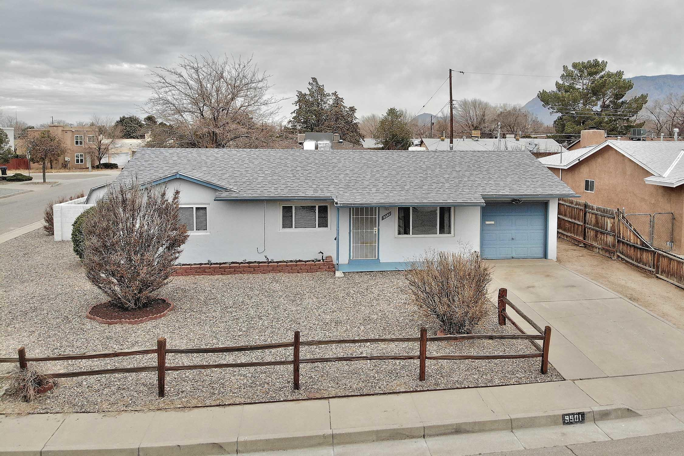 Charming NE Heights one story home, featuring 3 bedrooms, updated full bath plus 2 living areas. Freshly painted inside and out. Vinyl windows and slider by Accent windows. New carpet in the bedrooms. Cute open kitchen with breakfast bar. Enjoy a large corner lot with gated backyard access, two sheds plus a covered patio. Plenty of room to store your RV.  Main living area featuring a wood burning fireplace surrounded by bookcases, opens to the backyard through a sliding glass door. Roof replaced 2017 on the main house, covered patio, and large shed. Installed refrigerated air and heat combo 2016. Lots of beautiful flowering bushes and shrubs. Nice wide streets perfect for walking, with two parks within walking distance! Quick access to freeways, KAFB/Sandia Labs,