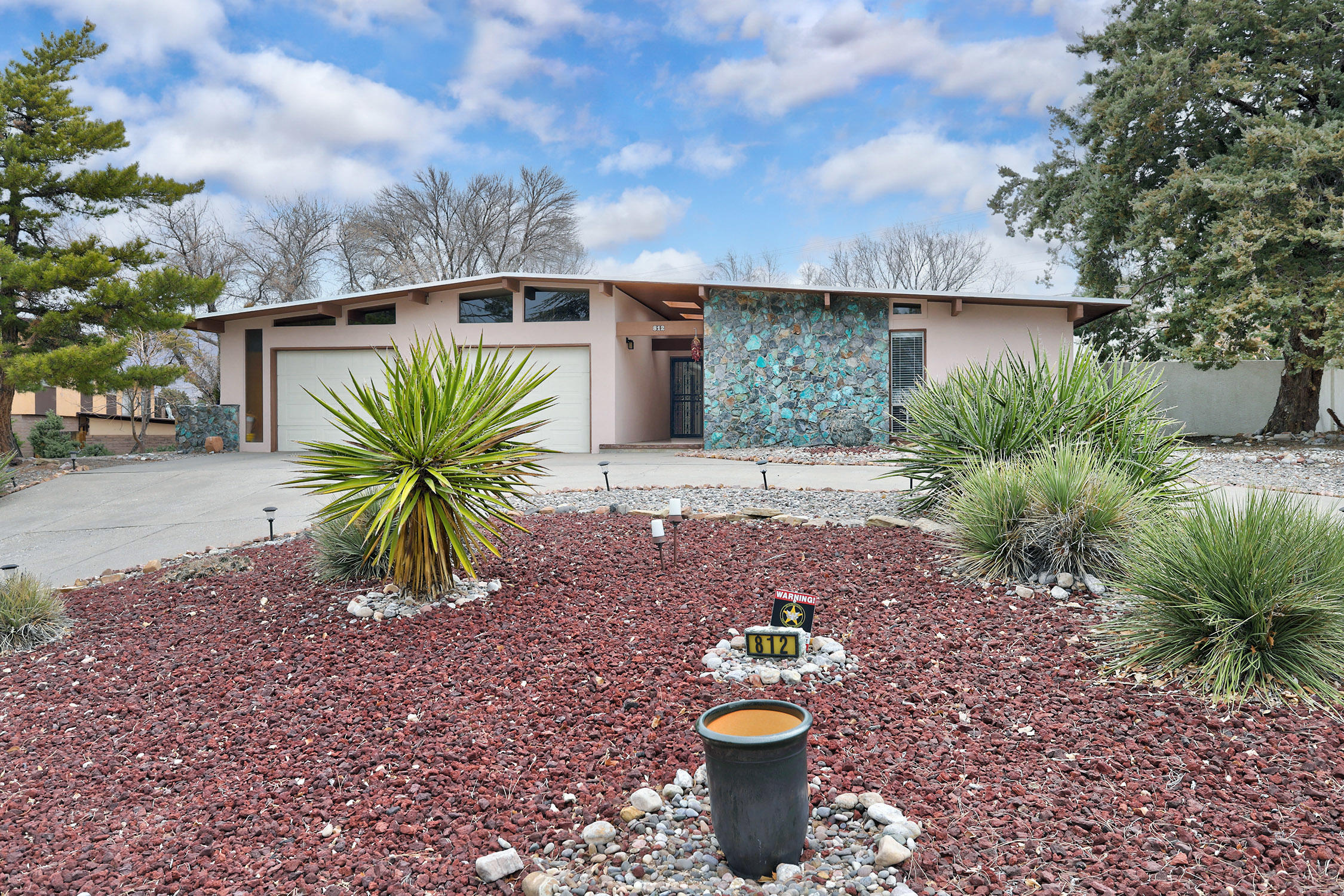 A Mid Century Modern, Light Filled, UPDATED BEAUTY with a gate to the Golf Course!!  Corner lot, circular drive, OPEN FLOORPLAN with gleaming wood floors and Tall tongue and groove ceilings!  Cook's updated Kitchen with SS appliances and OPEN to both Spacious Great room with stone fireplace and wet bar, Plus open to Dining Room with room for everyone.  Owner's suite has updated bath and large walk-in closet.  All Bedrooms have walk-in closets and front bedroom has an additional sitting area/office. Backyard is perfect for outdoor enjoying open and covered patios views and gate to golf course!! COME SEE!!