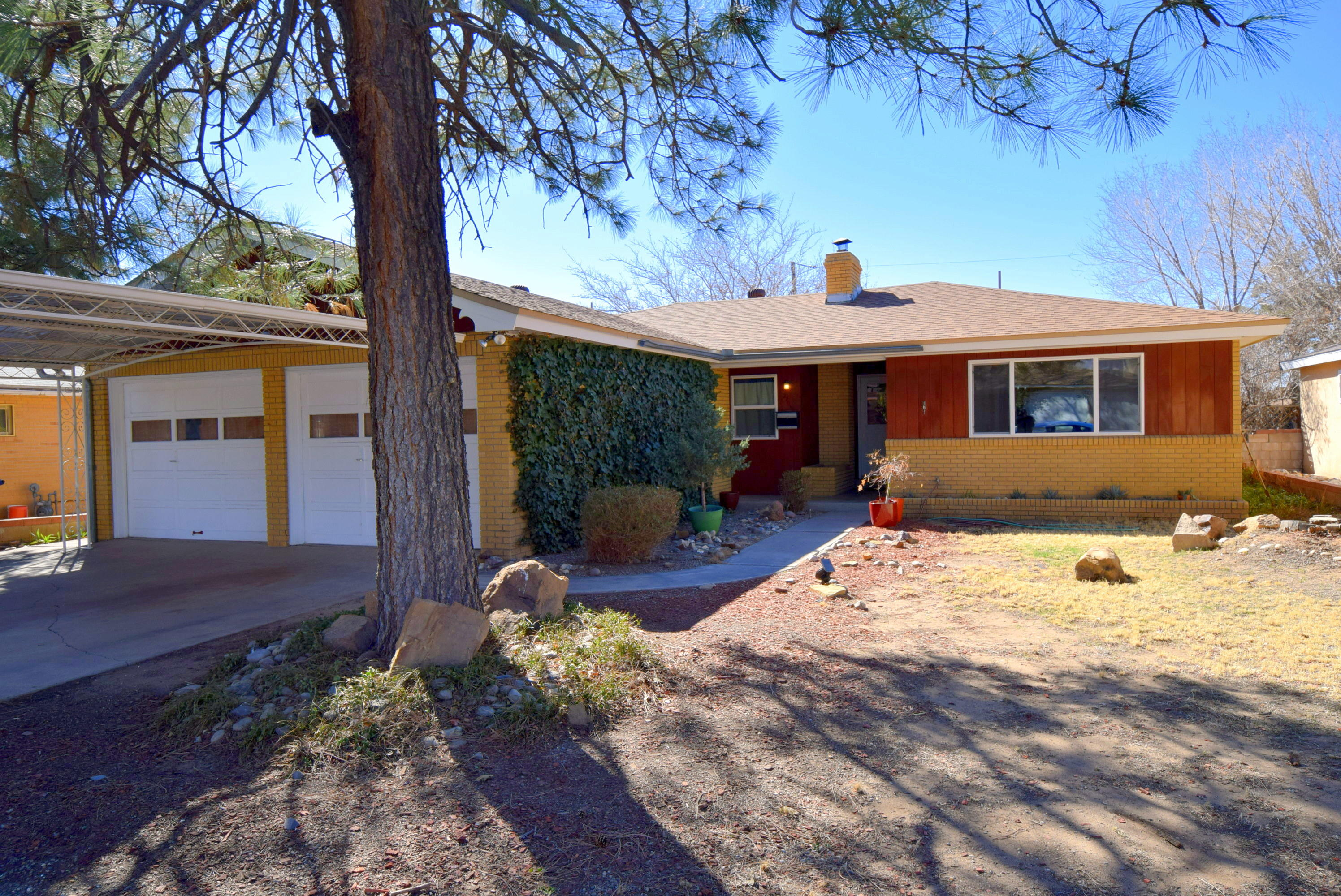 Fantastic uptown location. This all brick veneer  home is located in the heart of Albuquerque.  All three spacious bedrooms, a large living room and the hall have original hardwood floors. This house has a oversize double car garage plus a double car carport.  There is a wood burning fireplace in the dining/family room adjacent to the kitchen. You will love the separate utility room on laundry day. The roof, water heater, patio door and double pane thermal windows were replaced in 2017.