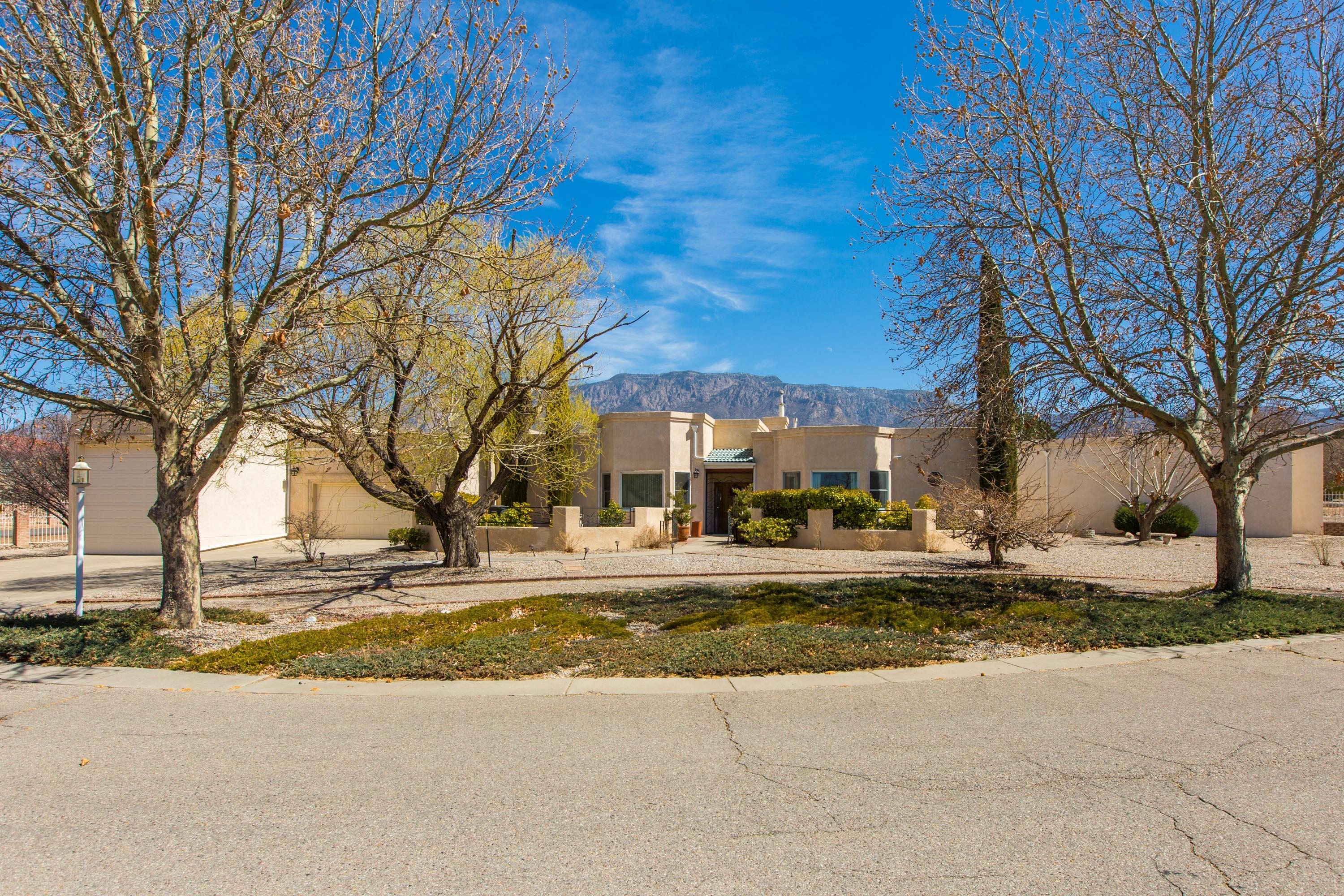 A must see in this gated North Albuquerque Acres neighborhood! Price to sell fast, this one story estate sits on a large .89 acre parcel with incredible Sandia Mountain views. Enjoy views from most areas of the home! One sprawling level of updated, airy and bright square footage includes a nice open concept floor plan with kitchen open to the great room. Sunroom is heated and has ample space for (482sqt) for a game room, entertainment room, etc. Two spacious master bedrooms, additional bedrooms, (2) office spaces and workshop and excersise room! The garage could fit 3-4 cars in tandem in the RV garage, with two additional garage spaces. Abundant storage space thougtout! Refrigerated air, central heating, new lighting, new appliances, granite countertops,  Low maintenace yard.