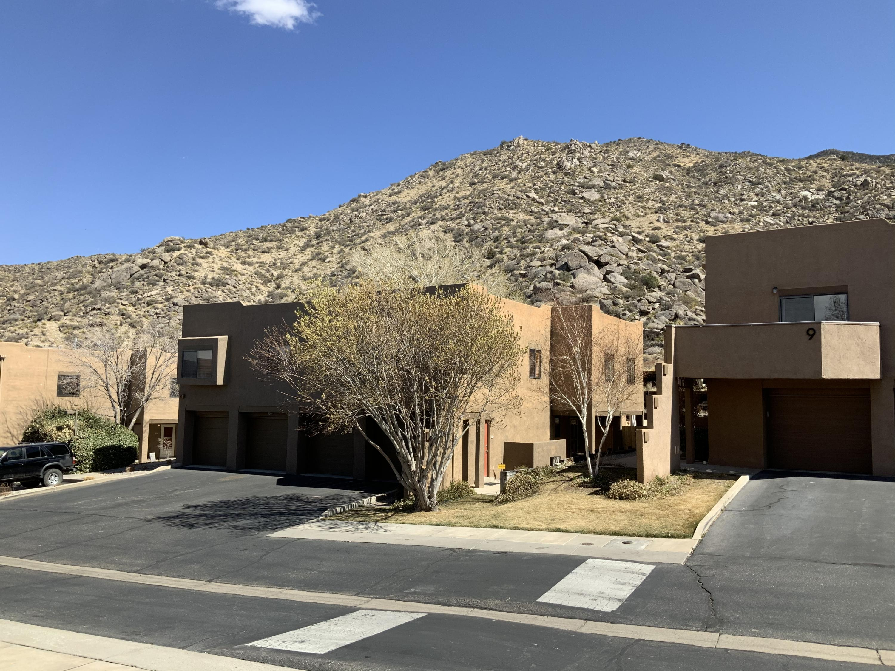 Updated Foothills home and End Unit which is SURROUNDED BY PARKS AND OPEN SPACE. Private backyard and Portal viewing the Sandia Foothils  & close to Casa Grande Linear Park Trail.... and connects to three additional parks, as well as, the Foot Hills Open Space. New upgrades including paint, GRANITE countertops, and more. All appliances including full size W/D stay. Refrigerated central air. Attached garage has storage and work area. HOA covers landscaping, building exterior maintenance, some insurance, and some utilities.This is a Really Nice Home!
