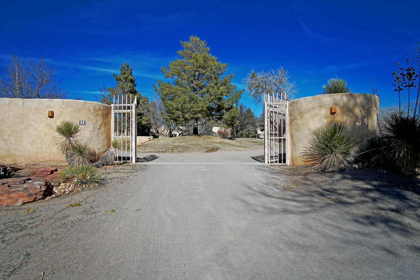 Picturesque 2.5 acre estate in Corrales Del Norte with sprawling lawns and big trees & stunning mountain views & direct access to hiking, biking & riding trails on Corrales bosque. Endless possibilities for adding separate studio/workshop, RV garage or even add to the existing vineyard. Enjoy country Corrales in a seclued setting with endless possibilities.This hidden paradise on the Bosque has adobe walls surround The entire 2.5 acres compound with a huge swimming pool,huge tennis court, wood windows,huge beams,high ceilings,marble floors,custom baths, and inside & huge outside hot tubs. The property consists of a 7500 sf main house and a 2500 sf guest house. Absolutley one of The nicest property in Corrales on the Bosque. Seller's personal items excluded & will not convey.