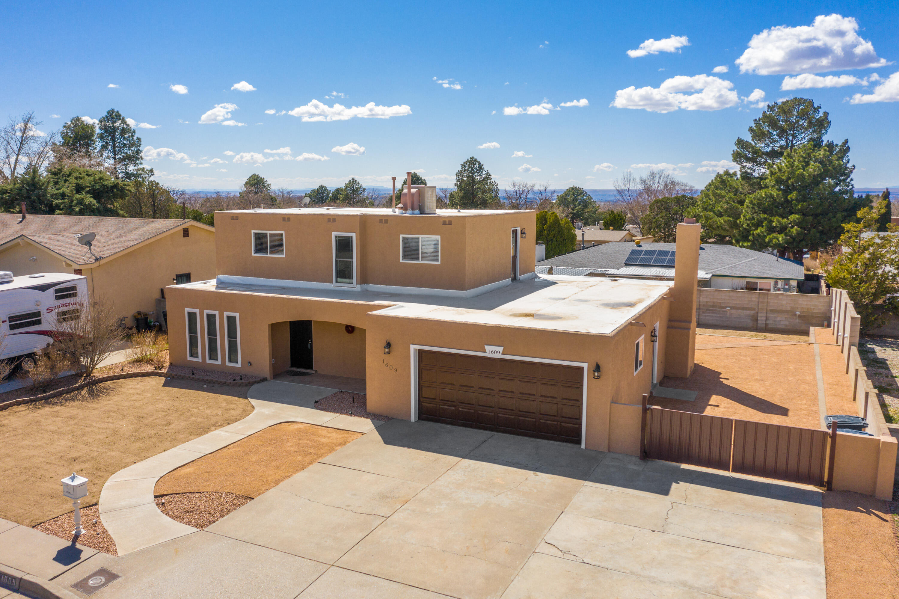 This 5-bed, 2-bath home has been remodeled throughout! The kitchen is open to the living area and amenities include custom cabinetry, granite counters, glass tile backsplash, s/s appliances, under sink water filtration, breakfast bar and large pantry. New carpet, wood and tile flooring throughout. Updated LED light fixtures and ceiling fans. Fresh paint and stucco. Newer evaporative cooler (2019). Updated doors and windows. 1 bedroom and remodeled bathroom are downstairs; the master, 3 guest bedrooms and remodeled bathroom are upstairs. The TPO roof (2020) is still under warranty! SW gravel landscaping in the front and backyards. RV parking. Please click ''More'' for additional information . . .