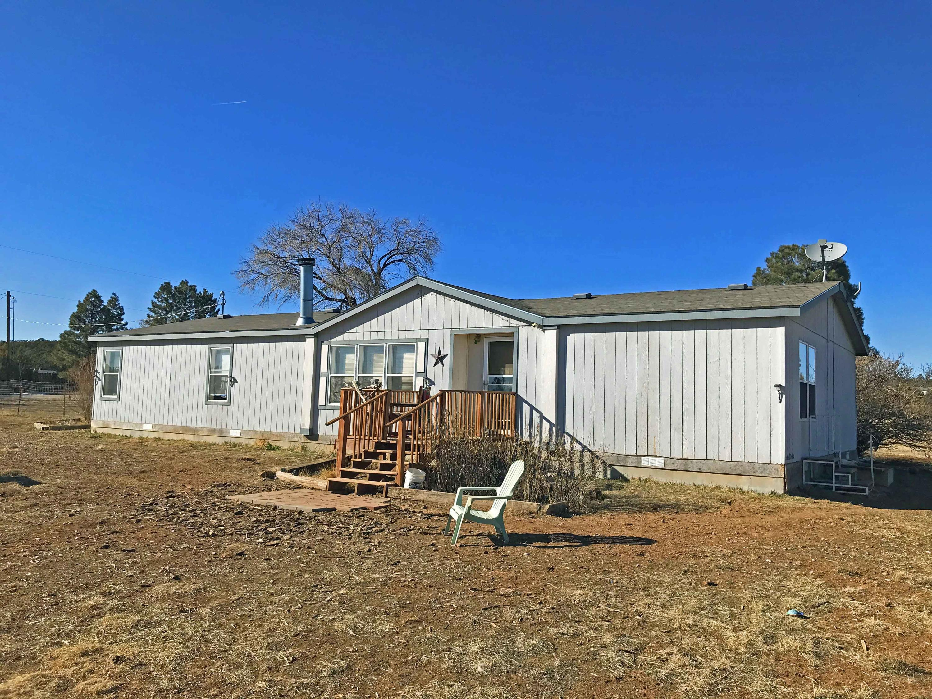 Here's a great place on 4 level acres in the East Mountains!  This 2006, 4 bedroom, 2.5 bath manufactured home is built for Wyoming winters with extra insulation, double windows and 2x6 construction.  It has refrigerated air as well!  The land is fully fenced and includes a 30x40 metal, 1,200sf garage/workshop that is fully insulated with 3/4 bath, a gas heater and evaporative cooler. Ceilings are 15' high and room for up to 4 vehicles. 500 gallon propane tank is owned.  200 amp electrical, well, and septic.  Fruit trees and additional storage sheds.  Needs new flooring, paint, etc. Property sold ''as-is'' condition and priced as such. If your looking for a great deal, come check this one out.