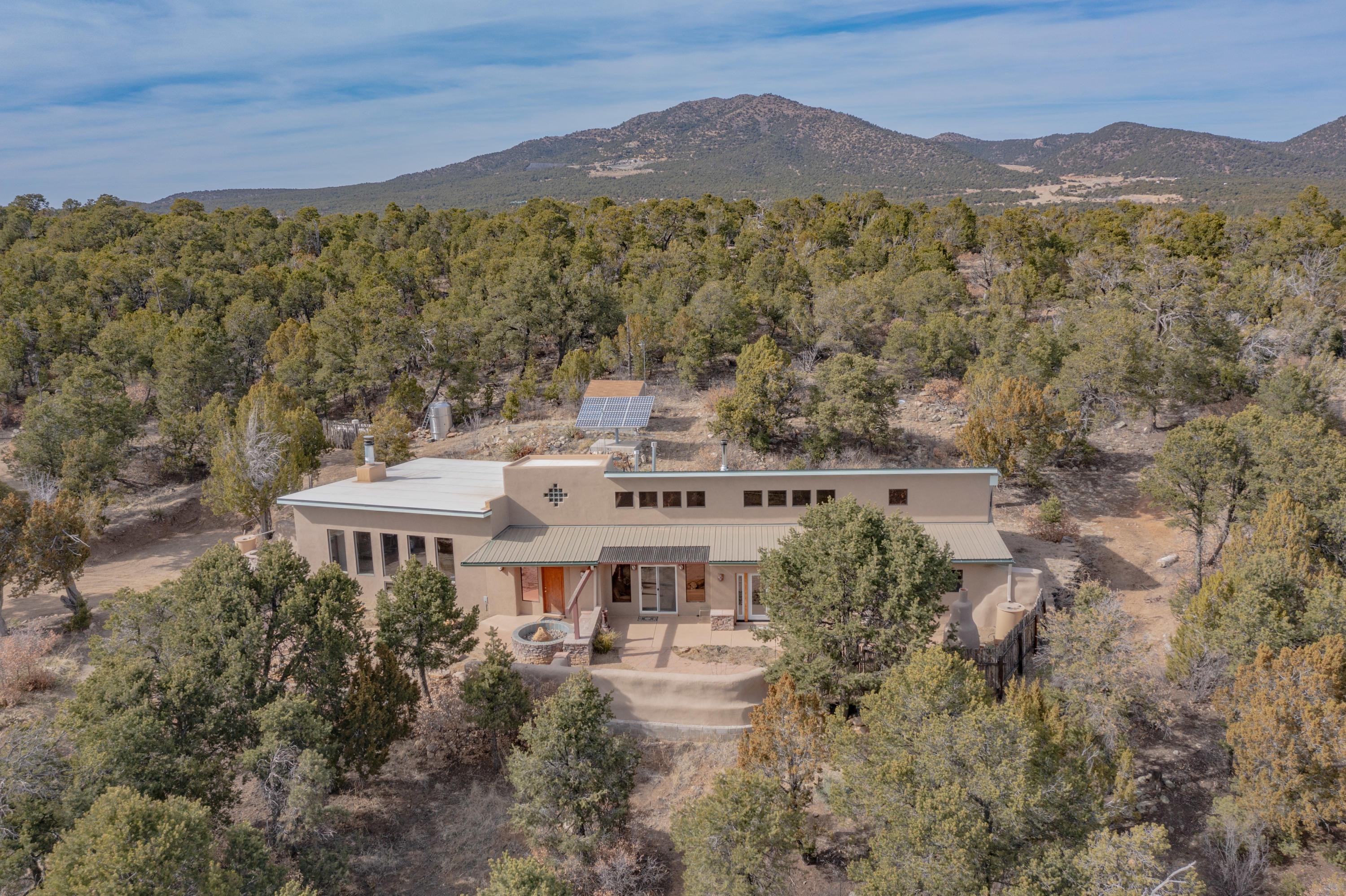 Get out of the city & enjoy fresh mountain air scented of pine trees. Breath deep, relax, & meditate to natures music. Off the Grid passive solar designed home. Conventional Financing available. Extremely private, 7.6-acres fenced w/solar powered remote-control gate access. 35 mins from ABQ & 45 mins from Santa Fe. 1200 tires rammed w/3,500 tons of adobe dirt. Interior walls covered w/ adobe mud. Exterior walls covered with 1' foam board insulation & 3 coat stucco. South facing wall is 2X6 frame const w/ Icynene insulation & dbl pane safety glass. Custom kitchen w/Hickory cabinets, granite counters, Premier 36'; 6 burner gas range designed for off-grid. 26 cu/ft propane refrigerator. Living/dining room is 1,000 sqft w/ massive fireplace, in-ground 900 gallon water tank & waterfall feature.
