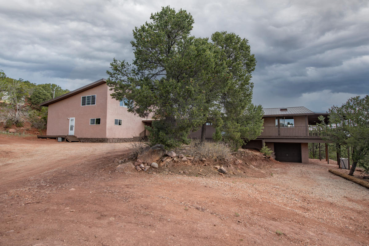 Absolutely magical. Completely-renovated mountain retreat a mere 20 minutes to ABQ Uptown yet worlds away! Enter through electronic gates and up the mountain to a crest with this sprawling residence. Step up to the wrap-around porch and take in peaceful views of distant mountaintops all embraced by the calming energy of trees. Ahhh... Cross the threshold and you'll know immediately: this is definitely the one.
