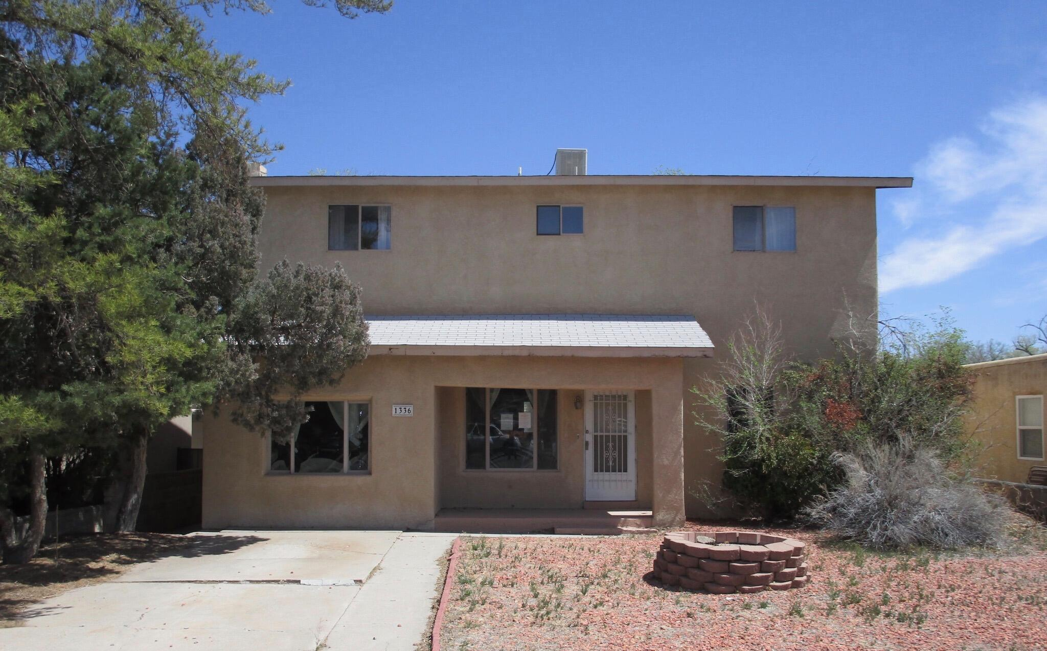 WILL NOT LAST!!!  Unique property has Guest House/In-Law Suite & Basement only blocks too UNM. The Main house on first floor has 3 bedrooms, 2 baths, and 2 living areas. Then, with a separate entrance, upstairs there is a COMPLETE other living quarters! Upstairs has 2 bedrooms, 2 baths, and a large living area with kitchenette/wet bar area, and dining room! Perfect for a mother-in-law quarters, guests, or Rental. But wait... there's more! A large backyard with storage shed along with an approx. 380 sqft. unfinished basement. You will not find another property like this in such a cool neighborhood.***No warranties or guarantees expressed or implied! Buyer to pay for their own Inspections for Buyers knowledge only!*