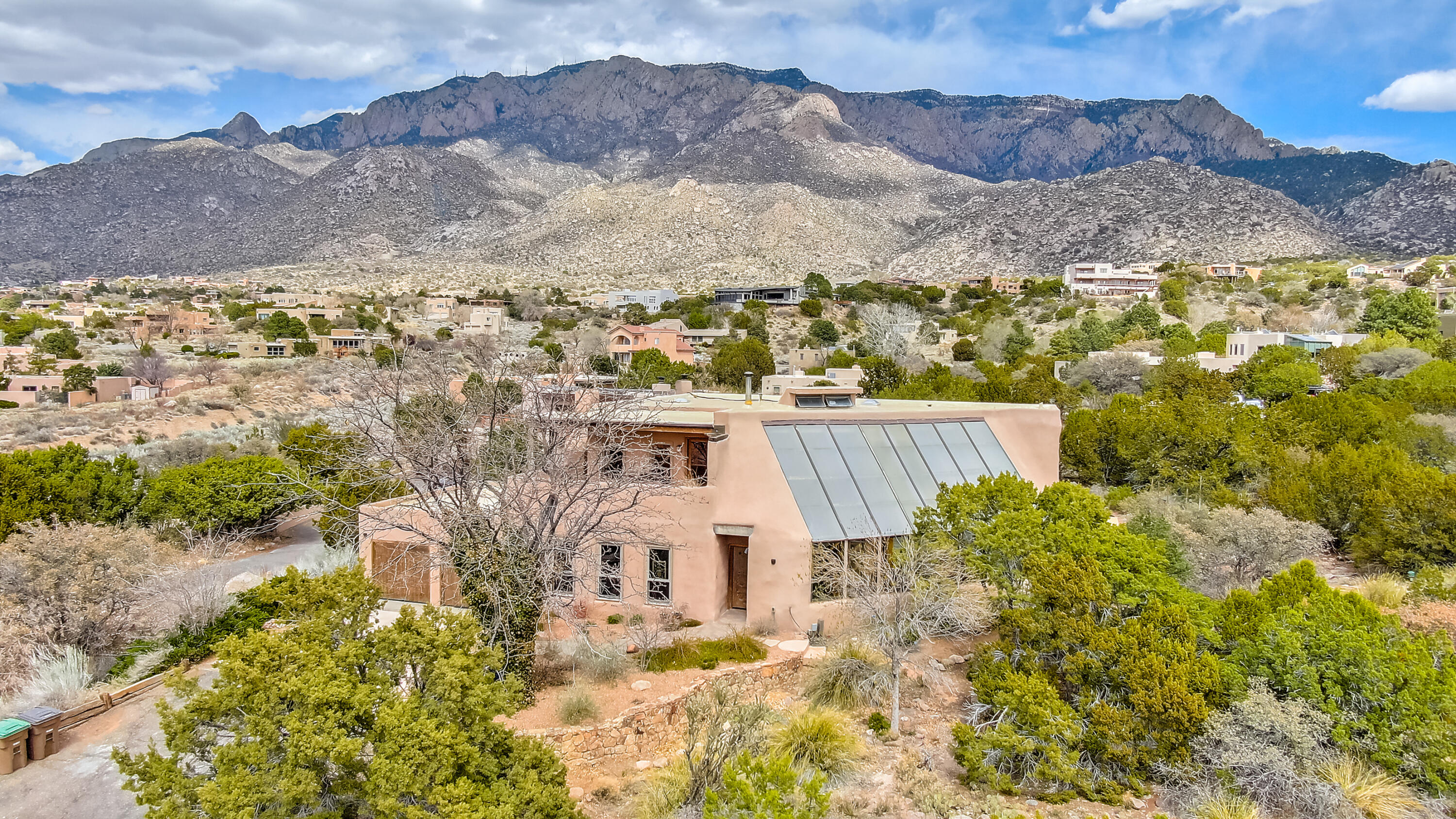 Way Beyond Ordinary - Pure Santa Fe charm / ambiance! Custom Adobe excellence nestled on a private wooded +/- .74 acre view lot at the Base of the Sandias just blocks to the National Forest.  Zen-like atrium / greenhouse will capture and ''soothe the soul'' with gorgeous rock and brick appointments, exceptional natural light, pond and huge passive solar heat.  Can't match the chef's kitchen with eye level Kiva fireplace and the private master's retreat with never ending vistas from the wrap-around view deck.  Four bedrooms, study/office, multiple living and dining areas, gorgeous latilla beam ceiling treatments, exposed adobe, Talavera tile and more pueblo charm at every turn. Feel the vibe- it's awesome!