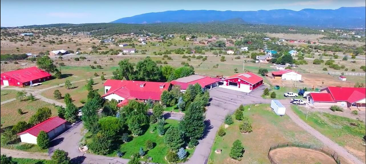 Lush Acreage subdivided in two parcels. Custom auto gate entrance with pipe fencing, secure, with paved driveways to Main house, casita with recreation room and state of the art Garage.  Solid oak cabinetry and granite counters, Oversized formal Dining room, Office or Living area, walk-in closets, 12Ft ceilings, Pella windows, radiant heat and skylights.  Green house attached with overabundant covered patio, fruit trees, 50 amp RV hookup, outside kitchen.  Casita with 1 bedroom, kitchen, and huge recreation or video room.  3 Car garage, and a  3-4 carport with an additional 50x50 finished auto showplace or Workshop with flooring and half bath.  Bring your horses, a beautiful 4000 sf Barn is surrounded by lush pasture and fencing.  Owner will consider financing options including a trade.