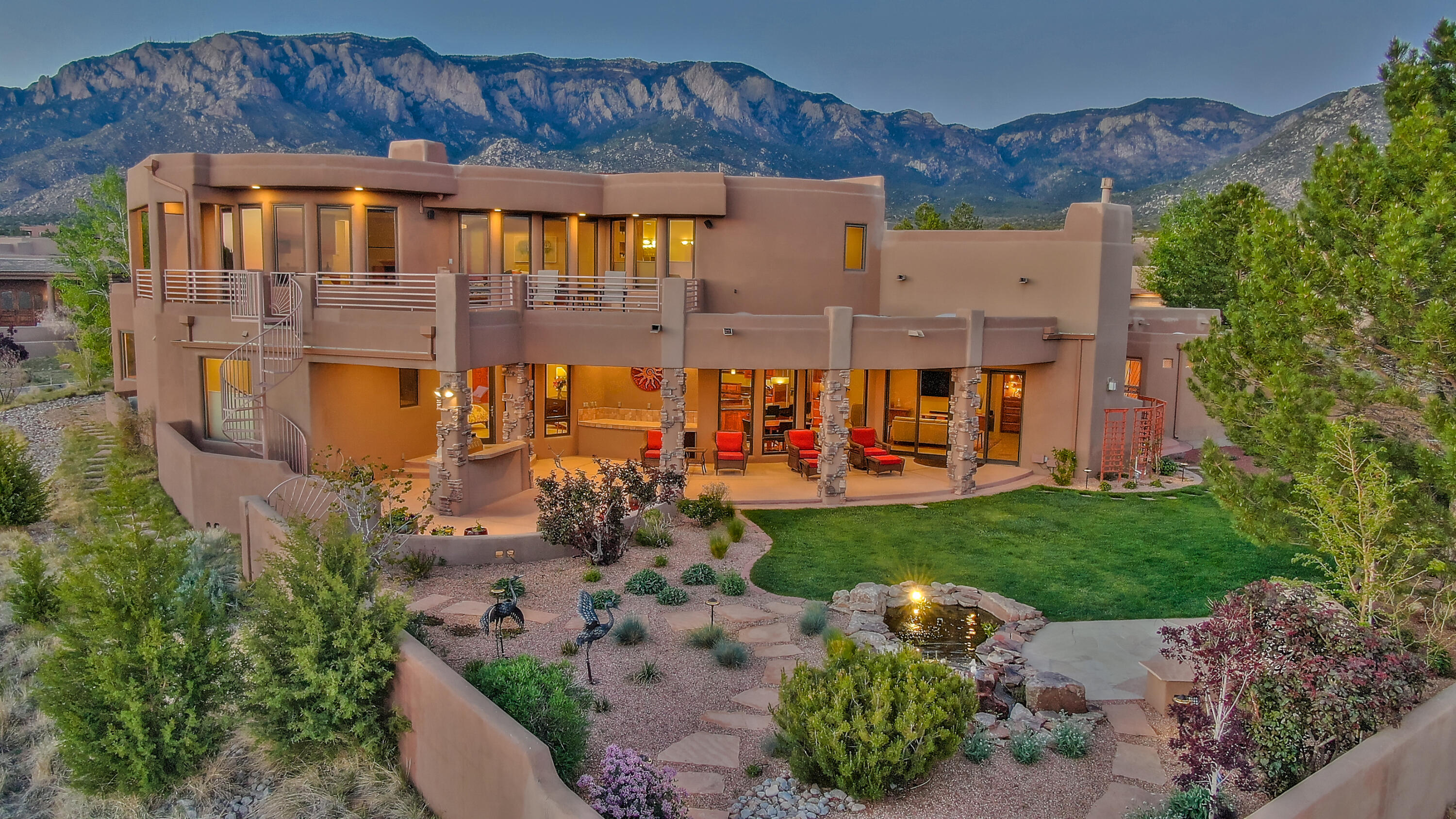 Breathtaking custom luxury home on a gorgeous, professionally landscaped 1 acre lot w/outstanding mountain & city views! Elegant architectural design by Eric Spurlock boasting an exceptional floorplan that will suit many lifestyles. 3 spacious rooms down including 1 ensuite w/jetted tub & patio access, expansive owners retreat up w/ luxurious bathroom & huge patio overlooking yard/city and a perfect office w/mountain views! Amenities galore; abundant in natural light, radiant heat, refrigerated air, extensive security & home automation capabilities, Chef's kitchen, greatroom w/2 dual temp wine coolers, superior outdoor living spaces, soothing fishpond, 2 rock fountains, aspens, pine, roses, outdoor banco, cool grass & room for a pool! It's a High Desert gem  & could be your ABQ Dream Home!