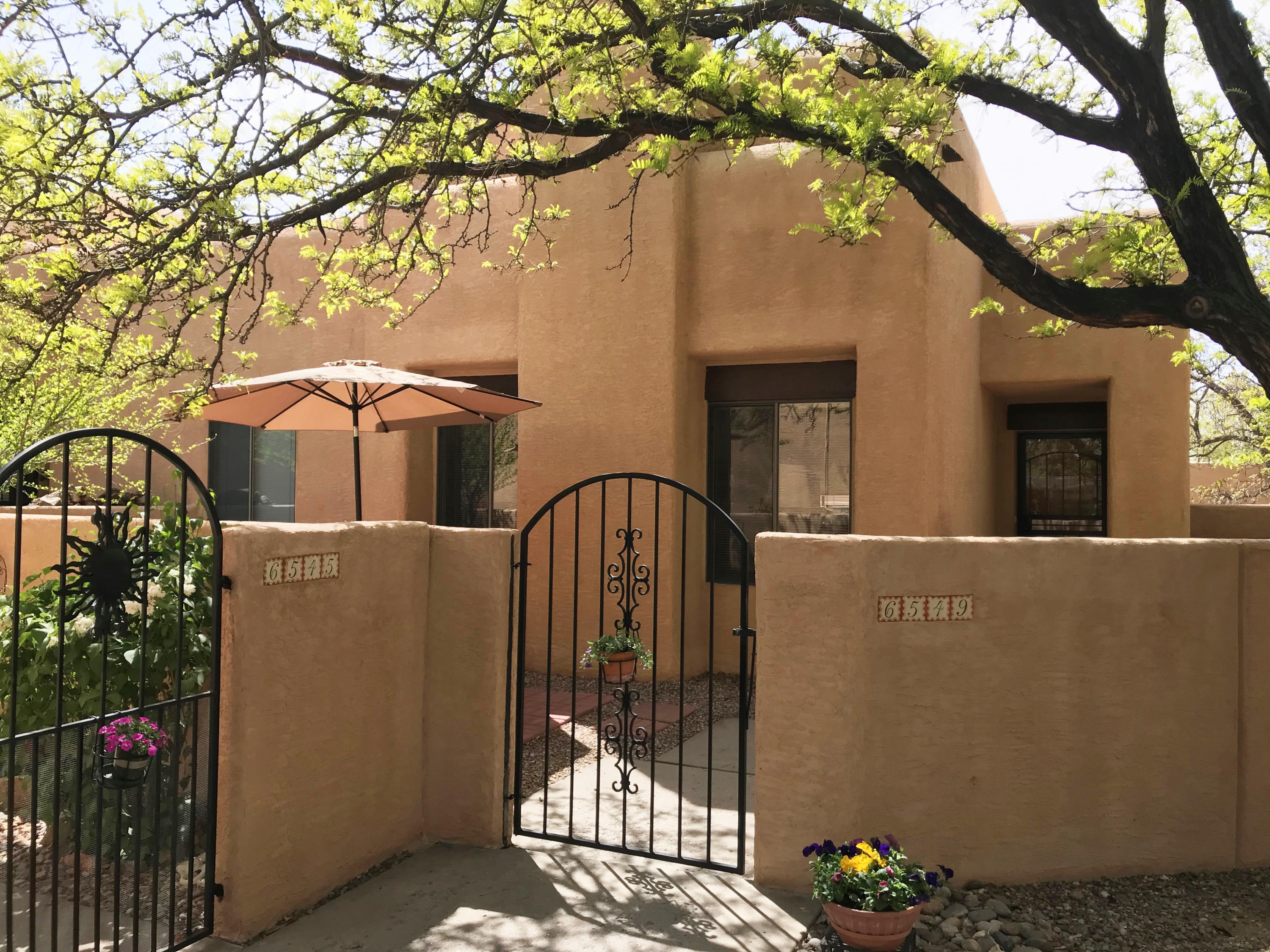Fabulous quiet location within El Paseo away from Academy and Eubank and situated in a private nook away from the street.  Delightful courtyard entry with sitting area.  Trees in common area adjacent to property provide shade. High ceilings in living & dining areas which open to one another.  Tile in entry, hall, kitchen and bathroom. New refrigerated a/c and furnace in 2019. New stucco in 2020. New garage door in 2020. Washer, dryer, refrigerator, 3 umbrellas, rain barrel and outside furniture stay.  Private inviting backyard with 3 sitting areas that backs to landscaped common area. HOA includes stucco, garage roof, common area, club house and swimming pool ($230 monthly). Ecobee heating/cooling system. Walking distance to shopping, bus routes, restaurants & Academy Hills Park.