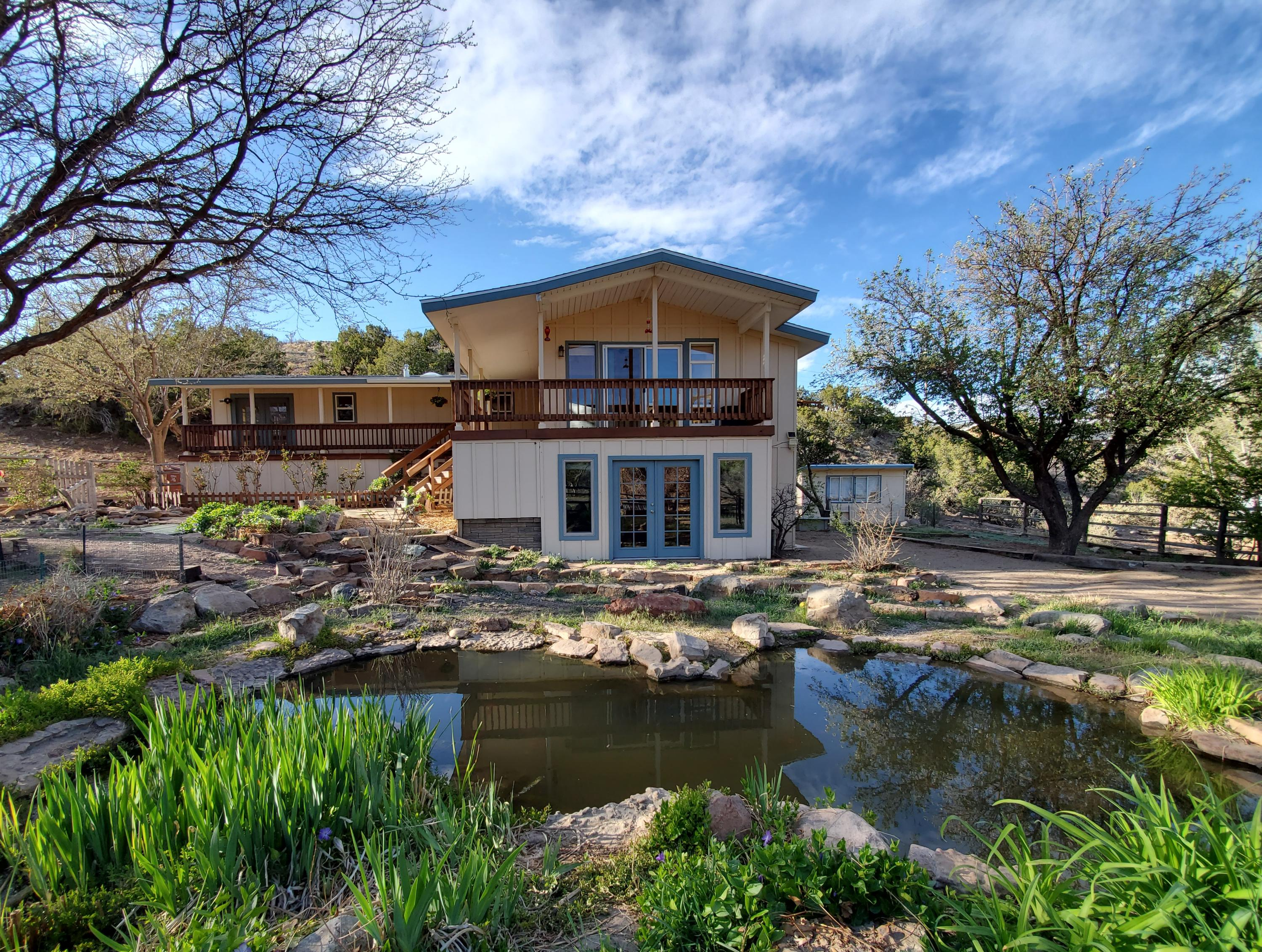 Open House Sat 11-3 & Sun 11-4.Freshly repainted ranch style home, 3-4 BR,1 3/4 bath with wonderful views of the Sandia Mountains nestled in a  private area supportive of gardening & livestock. Rustic wood-burning fireplace in living room with refreshed oak wood floors throughout. Open modern kitchen with stainless steel appliances. Walk-out basement with French doors opens to relaxing lily pond. All other rooms are on main level. Covered wrap-around deck. Storage sheds and modern chicken coop (which is currently home to mother cat & 3 week old kittens so please don't open door but peek thru the window). Horse area. Garden & Fruit Trees.Membership in the Las Huertas Community Ditch Association, which provides irrigation water to the property, can be obtained by paying new membership