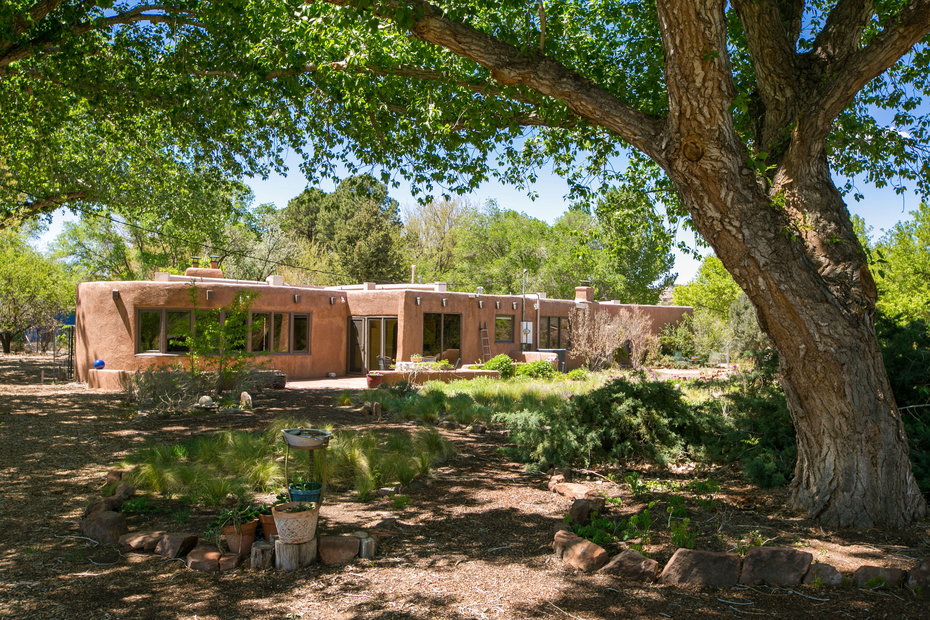 Fabulous adobe on a beautiful south endCorrales acre.  Nestled under the cottonwoods,  this is a real charmer.Beams, T & G,  4 kiva FP's, brick floors, saltillo, niches, bancos and more!  Courtyard entry, greatroom, dining room, stepdown bonus room w/FP,  primary suite w/sitting area, oversized shower, private courtyard, banco, & FP,  spacious 2BR, full bath, family room/den, separate 3BR or studio,  2 car garage, carport.  Access to backyard, which is beautully designed for the gardener and nature enthusiast.   This santuary offers plenty of room for your animals.  A terrific home for entertaining both inside and out.Only minutes away from shopping, hospitals and access to our Corrales trails & bosque.A true adobe on a southend private location.