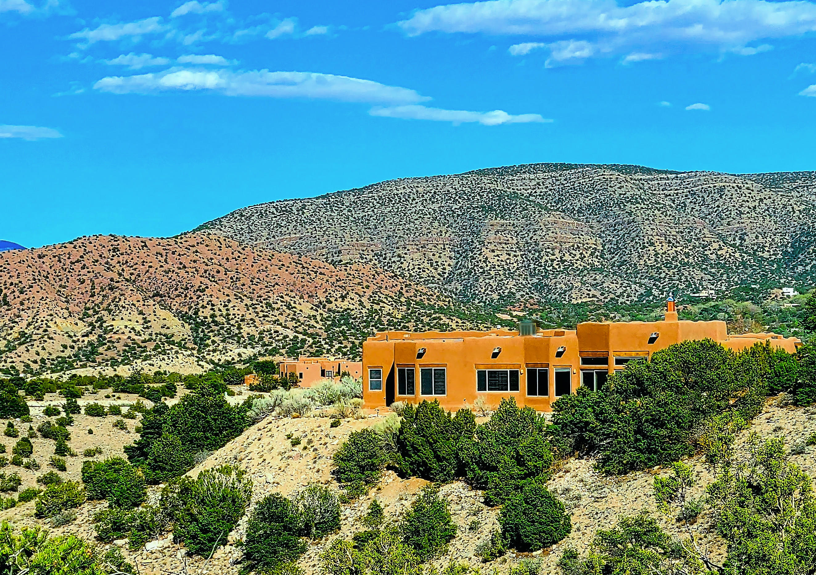 Perched hillside with million dollar views in upscale Placitas community of ''The Overlook'', This top notch custom home is a tasteful celebration of life in the Desert Southwest & bursts w/charm & character. Walls of windows & doors take in the color filled skies, mesas & mountains. The thoughtful design offers a large great room & open dining room w/pass through bar to the kitchen, at the center of the home. 2 spacious guest rooms + shared bath are on one wing of the house, and the master suite and adjacent office/4th bed & ample storage on the opposite side. Oversized Garage w/workshop, Tankless H20 Heater & H20 Softener. Bonus storage room w/built-ins & plumbed for Dark Room Equip! Multiple flagstone patios on  all sides of home. New Mexico True finishes. Special Features List Attached