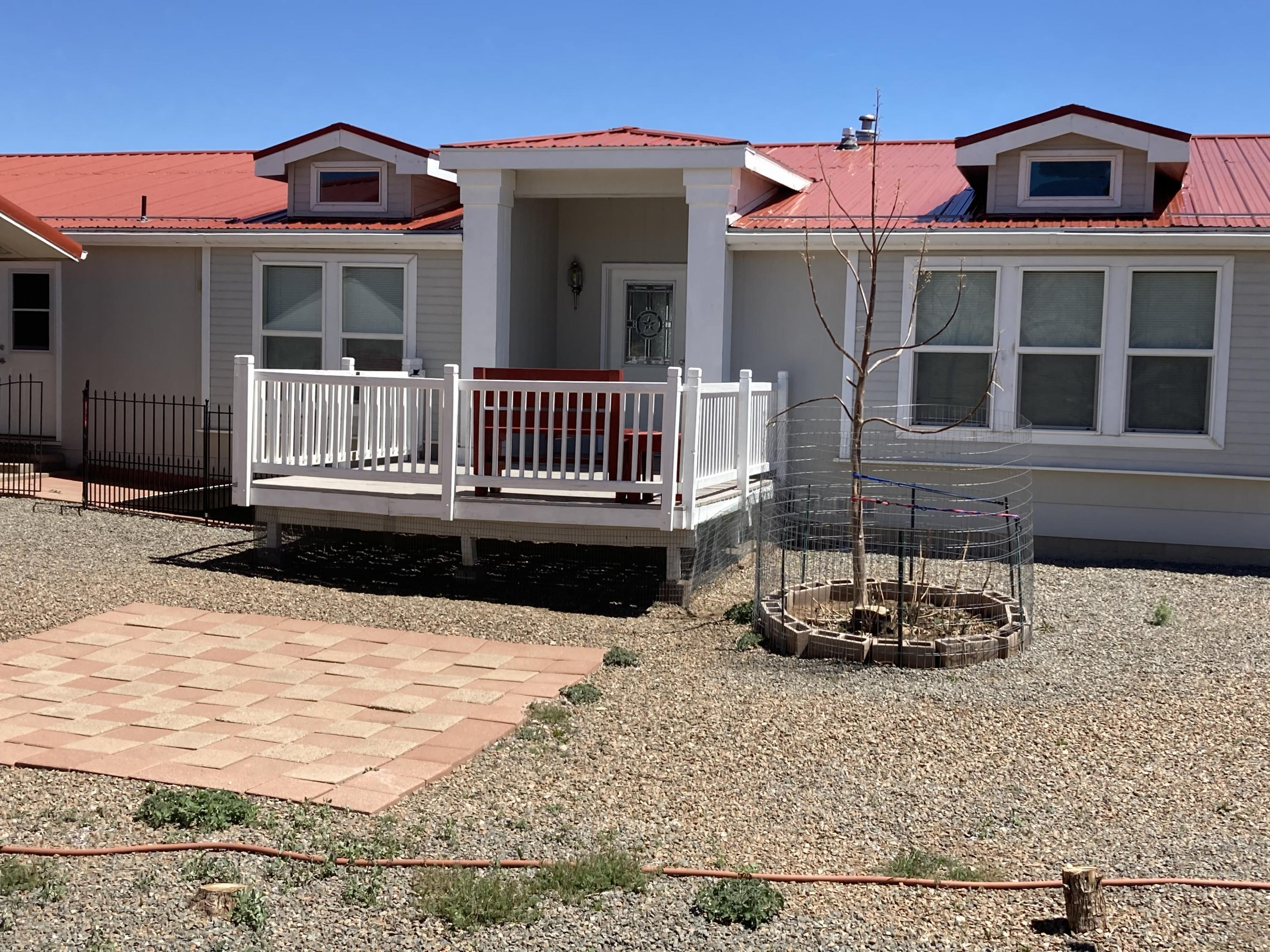Welcome to the East Mountains! This home has so much to offer. The sale will include to seperate 10 acre lots. The home is a Karsten triple wide with 2x6 walls and is 2720 sq ft which includes a living area and family room, four bedrooms a huge kitchen with lots of cabinets with tile and  a kitchen island and breakfast nook. All the appliances stay.  You'll enjoy the views from the living area or the master bedroom. The deck is perfect to enjoy being outdoors. There is a 2 car garage and a 20x30 workshop, a two car carport. There are also two separate out buildings for crafts or other products. Theres a nice rainwater system with 13000 gallons of tanks. Make this home yours before its too late!