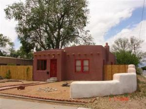 Charming Pueblo style home built in 1941. New TPO roof to be installed mid-May, Hardwood floor throughout,, many vintage details wood moldings and doors, plaster arches, and great wood-burning fireplace flanked by windows. Light and Bright many Original Wood Windows. Kitchen has recessed Lighting, Open living/ dining area. Private flagstone side patio, Haybale exterior wall around side and back yard. Large back yard with fire pit, pergola, and gated alley. entrance.  One car detached garage and Workshop Area. Three Blocks to UNM. Five minutes to Nob Hill.