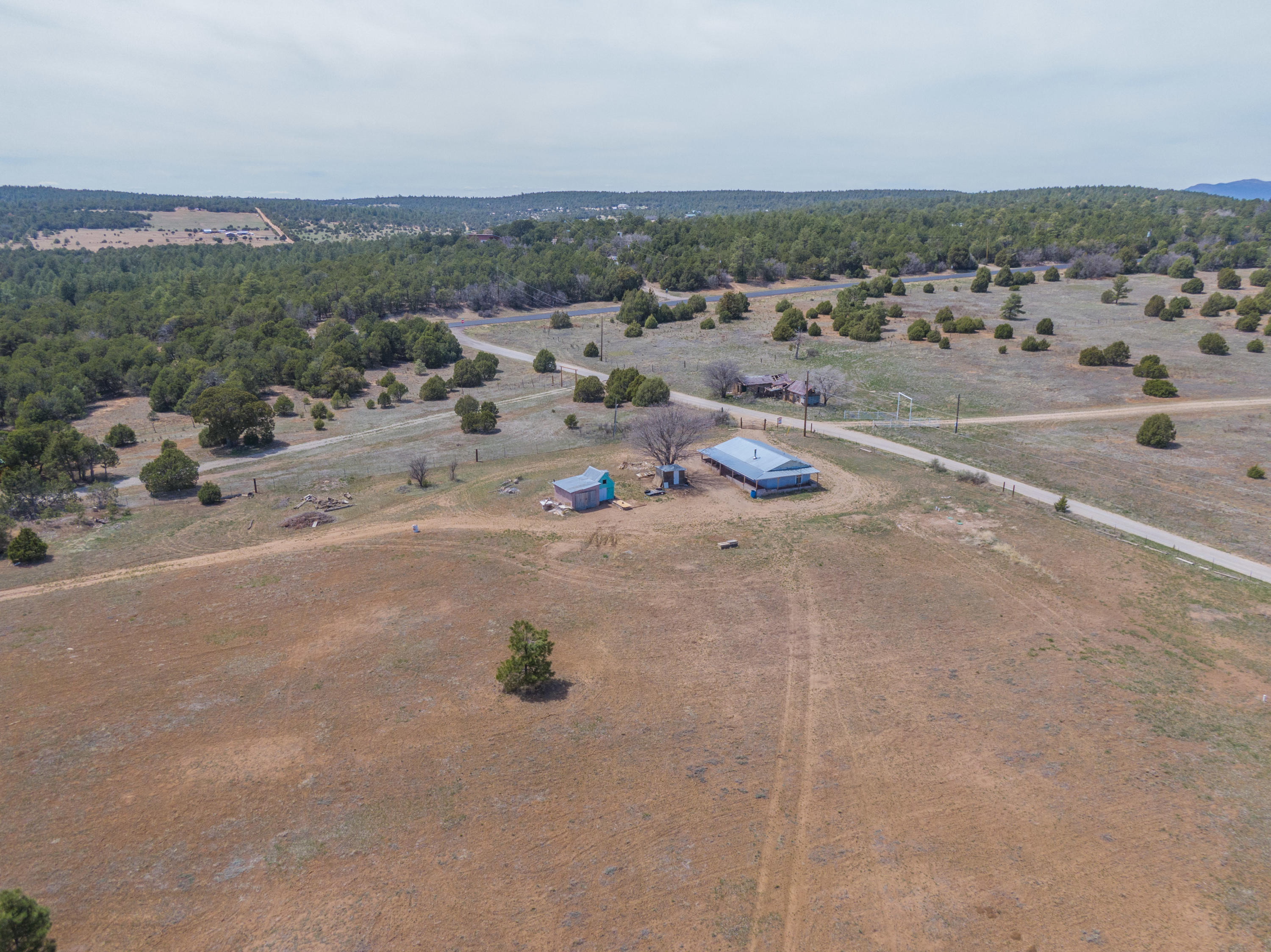 Build the mountain home of your dreams on this fully fenced 8 acre property! 900sf foot home with 2 bedrooms located on the front of the property makes the perfect for those weekend getaways. 2 wells on the property! Storage sheds. Close to National forest trail system perfect for hikers and bikers!