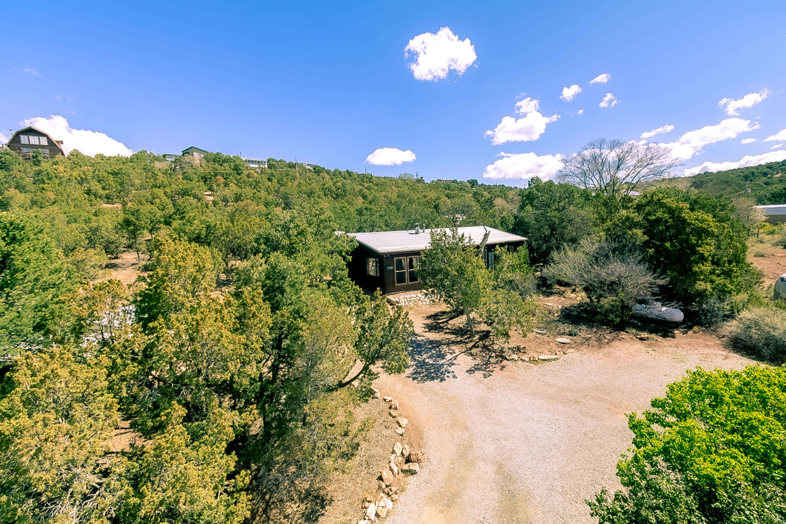 This mountain retreat home located in Sandia Knolls is surrounded by mature pinion & juniper trees. Open floor plan offers lots of options for decorating. Living area features tongue & groove accent wall, built in bookshelves & wood stove. Beautiful oak cabinetry in kitchen w/ tile back splash & laminate flooring. Owner's suite includes walk in shower w/custom tile surround.,new marble vanity top, sink, & faucet Large walk in closet plus French door out to wooden deck. 18'' of extra blown in insulation in attic. Thermal pain windows w/some updated to vinyl on south side of home. Metal roof. Flagstone patio area is great for relaxing & taking in the serenity. Separate dog run. 16'x8' storage building plus 22'x10' workshop/storage w/ electricity. This home has it all & 17 mi to Albuquerque.
