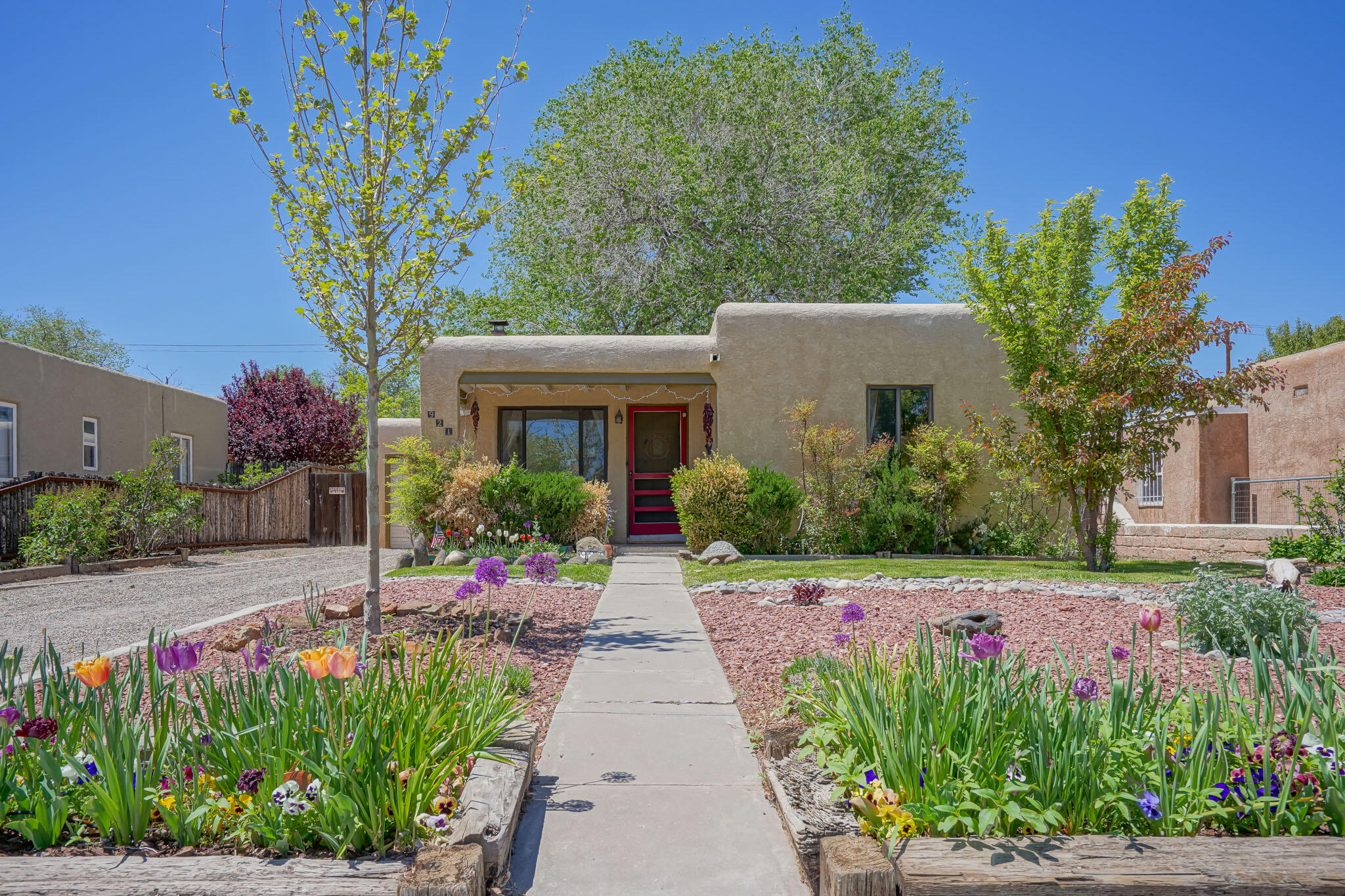 This adorable Ridgecrest property is conveniently located close to shopping, schools, airport, university, dining and freeway access. Walk or bike down to Nob Hill, or picnic in one of the many parks within a half mile radius. Enter and enjoy the natural hardwood floors, coved ceilings, Kiva fireplace and updated kitchen! New paint throughout and new carpet in the master bedroom which offers a large his/her walk-in closet!! Attached 1-car garage is complete with a workbench and large pantry. Step outside to the backyard, completely landscaped with lawn, raised garden beds, a greenhouse, and storage shed! Enjoy peaches, cherries, apples, and blackberries all from your private, fenced oasis. The patio are entertaining spaces perfect for any gathering! **No showings after Thursday Evening**