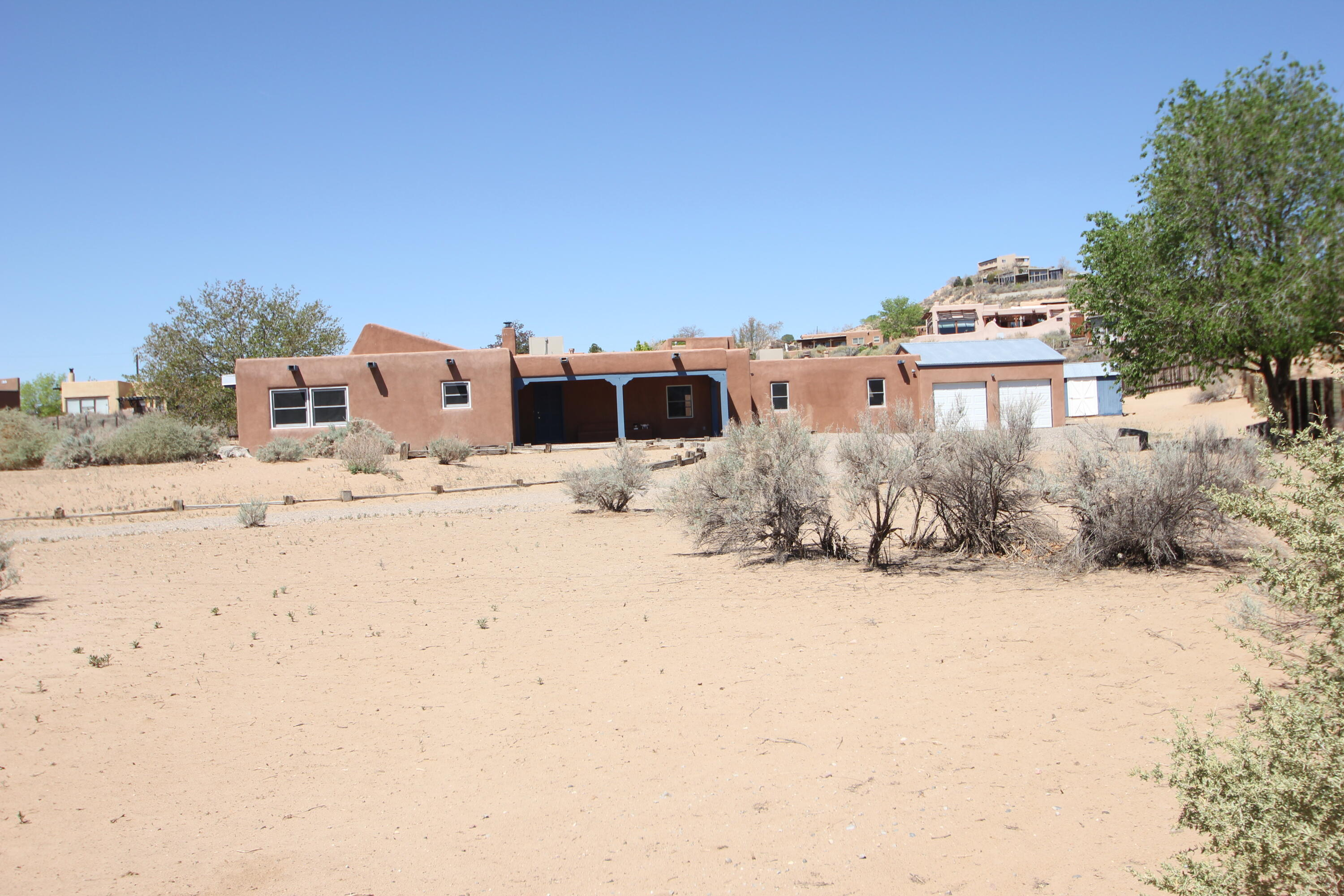 This is a Wonderful Santa Fe Style home, Features Vaulted Ceilings, 12' Adobe Walls, Rough-sawn Beamed Ceilings, Brick Floors and a private court yard . South Facing Wall-of-windows acts as a Engineered Passive Solar Feature.
