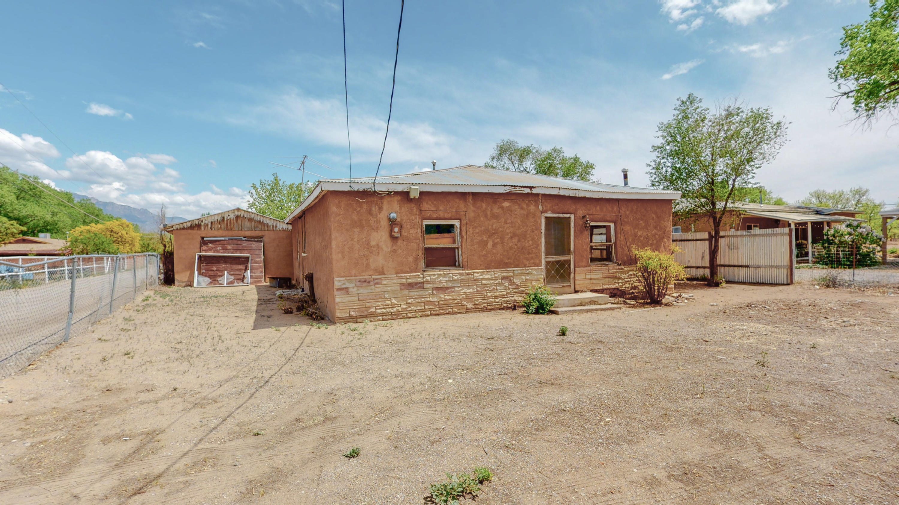 Diamond in the rough!!! Imagine the possibilities! Restore this tin roof casita on the EAST side of Corrales Rd & turn it into a charming Airbnb!  Vigas, wood floors & Mountain views off the back porch. OR, tear down the house & build a new home. Home is NOT HABITABLE. Enter at your own risk. NO CHILDREN are permitted during showings. There are big gaps in flooring from previous work that was started & not completed.   PLEASE NOTE - due to lot size, the Village limits new construction to the exact same footprint of the existing structures. You cannot make a two story.     PLEASE NOTE - due to lot size, there are limitations on type of  septic system.Buyer to conduct own research as to what can happen on this lot. Seller guarantees nothing.  Lot size estimated. CASH ONLY.  AS IS.