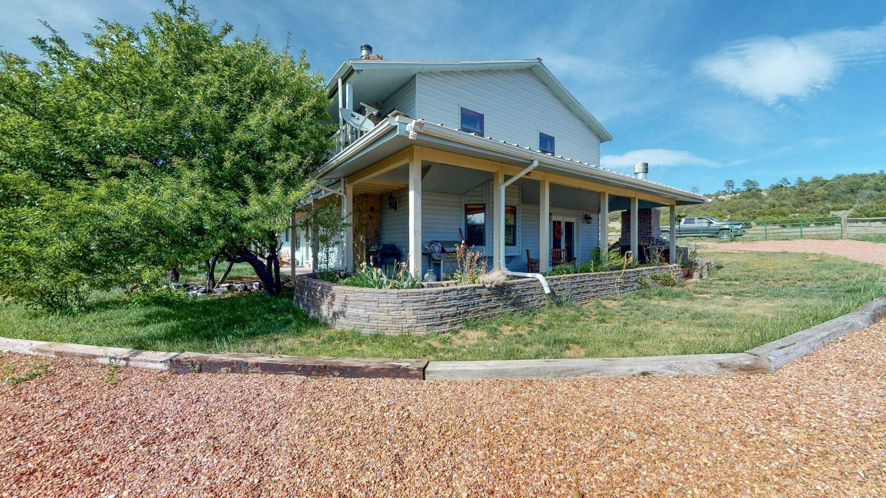 Only 20 minutes from NE ABQ busy streets, a haven awaits. Welcome to this beautiful 2-story home with views, completely fenced horse property, partially bordered by fruit trees, all sitting on 2 acres. This quiet 3100+ sqft home features a wrap-around covered porch, an open concept main floor, 3 wood burning fireplaces and formal dining area. 2 floor features large master bedroom with walk-in closets - walk out onto the full-length cover balcony with endless views, perfect for starting or ending the day. Sits on a dead end street so traffic does not run through. One car garage attached to main house and 2 car garage attached to workshop. Workshop, OR see it as a blank slate, is propane ready! Features sink, cook-top propane stove, wood burning stove and 1/2 bath. Estimated at 1074 sqft.