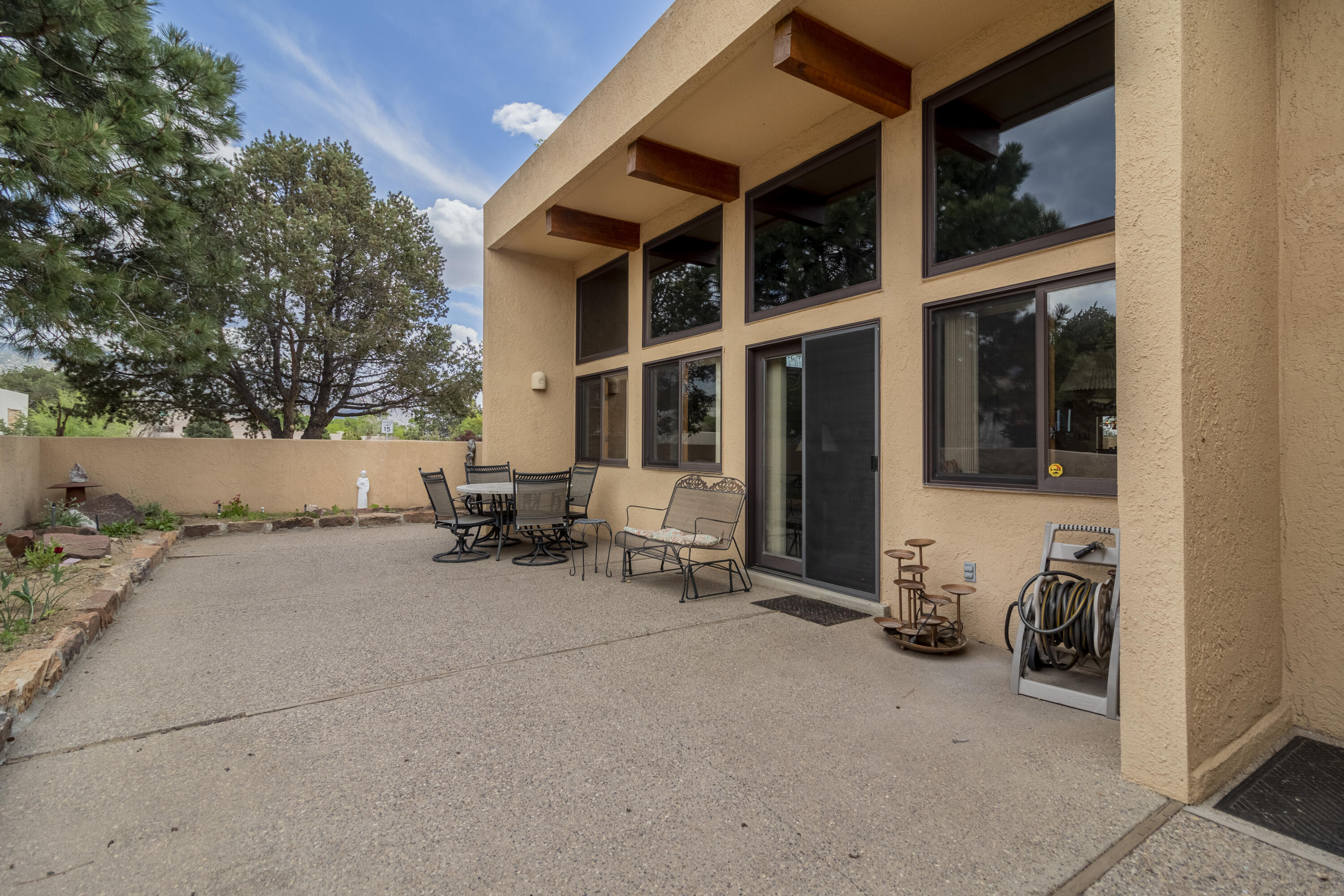 Open Saturday, May 8th 1-3pm. Single level 3bdrm/2 bath  patio home built by Roger Smith . Located in sought after SANDIA HEIGHTS with absolutely STUNNING MOUNTAIN VIEWS AND GORGEOUS SUNSETS. A large  welcoming courtyard leads you  across the threshold into the very light and bright  great room with beam ceilings, gorgeous FP, and wall of windows to enjoy the VIEWS.  Beautiful kitchen with granite countertops, wolf cooktop,  and large eating area. Kitchen also opens to the formal dining room. Primary suite which offers a 2 way FP  & extra flex space perfect for a nursery/office or sitting area, with it's own access to the covered patio and pretty backyard to enjoy those sunsets.   Extra wide 2 car garage w/2 work benches. Radiant Heat & Water Softener, Hot Tub is negotiable. Very Nice Hom