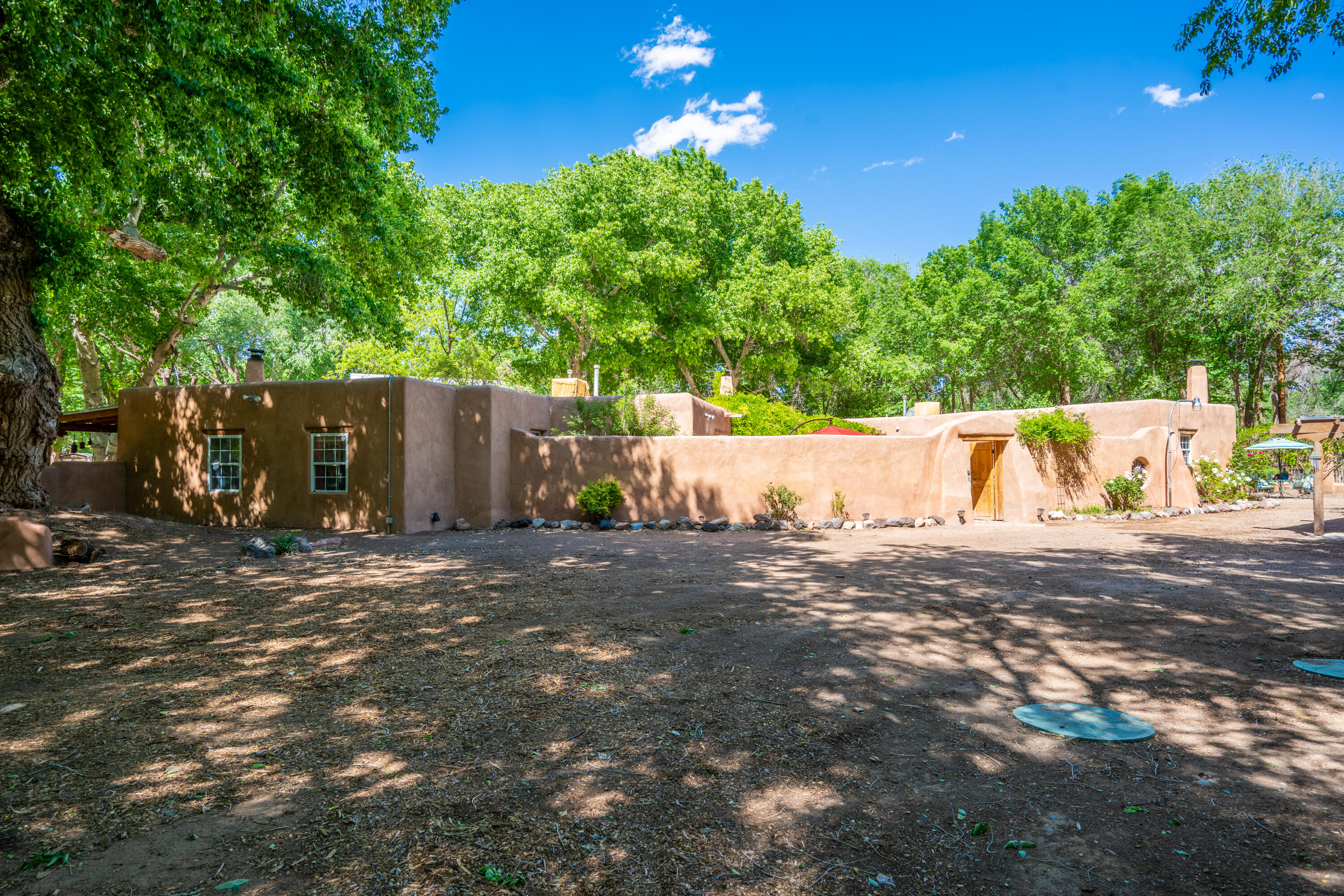 Incredible & Rare Gem in beautiful Corrales. This Secluded Adobe Home sits on 3.2 acres, lined with beautiful Sheltering Cottonwoods along this desirable private road. Updated open floor plan Kitchen, spacious Granite countertops & Island fitted with Newer Appliances, large pantry & wet bar. Two Spacious Living areas. Lustrous classic brick & tile floors Aloft Timber beam ceilings, skylights, five custom Kiva fireplaces  4Bedrooms possible 5. 3 bathrooms. Dreamy Garden courtyard for outdoor living & entertaining. This Rare property also provides extensive horse facilities to include an 8 stall barn, 2 Tack rooms, Arena, Pasture, Corrales ditch, irrigation & direct trail access. Great Big Workshop or Barn. This is your chance to live beautifully in the Enchanting Village of Corrales