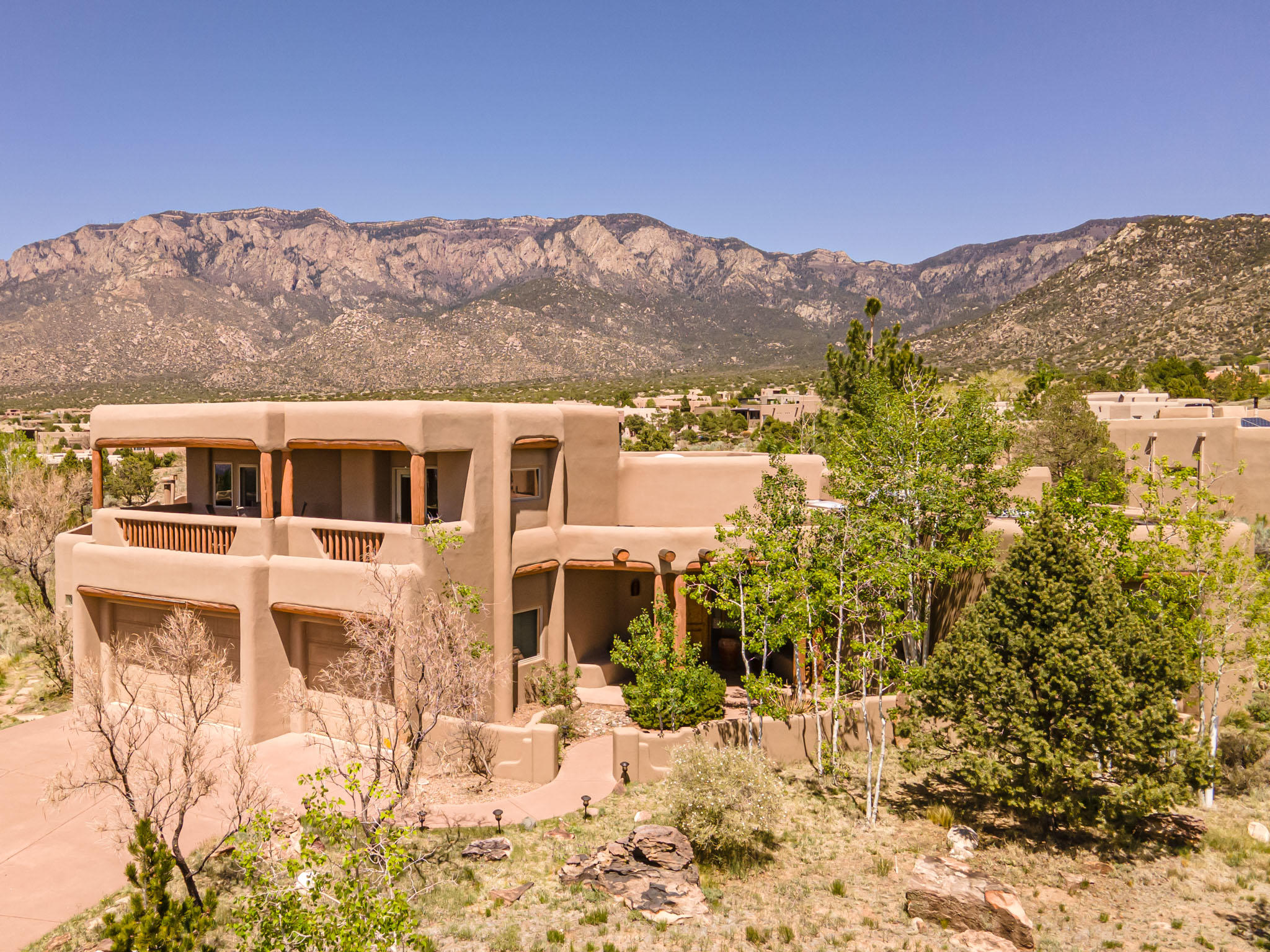 Fabulous Sandia Mountain & City Views from this gorgeous custom home on a .65 acres. 4 bedrooms, 3.5 baths. Private courtyard entry, stunning great room w/14ft wood ceiling & vigas,  custom fireplace, curved staircase, bancos, & diamond plaster finish walls. Elegant dining room, spacious kitchen, breakfast bar & nook. Owner's suite has a luxurious jet tub, big shower & walk-in closet.  1 add'l BR downstairs & 2 bedrooms upstairs that open out to a balcony with city views. Another balcony has city & mtn views. Lots of natural light throughout, raised ceilings, recessed lighting, lots of storage, radiant heat, refrigerated air & an oversized 3 car garage. Outdoor living at its best, enjoy the morning sunrise in your backyard oasis, spectacular sunsets & starlit skies, close to mtn trails.