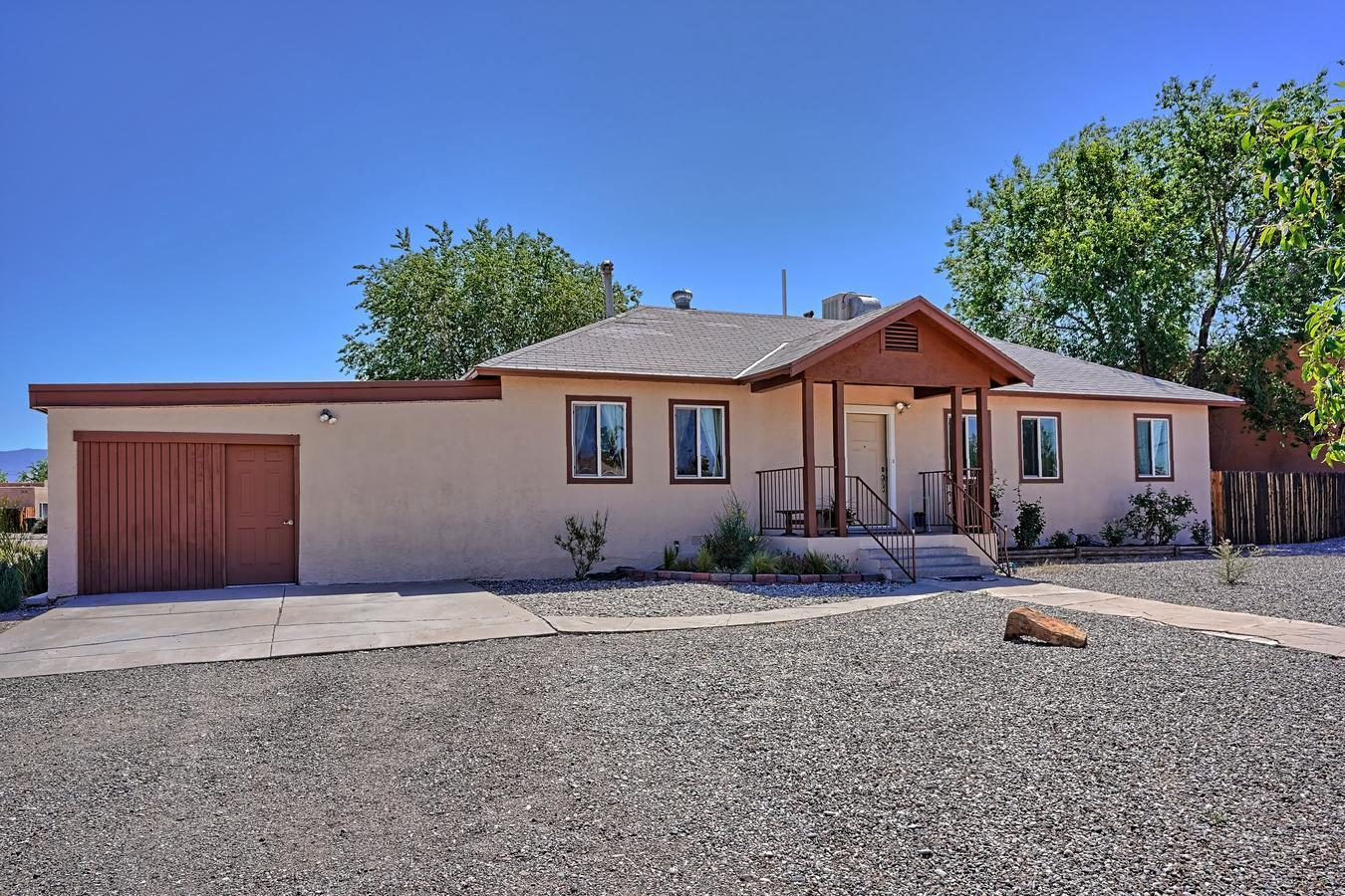 Convenient location with easy access to I-40 and Old Town/Plaza.  Large corner lot home sitting on .22 with privacy and views of the Sandias.  Update and move in ready.  Private side garden off master bedroom with French doors, full bath  w/2 bedrooms & full bath on other side of home for separation.  15 x 20 deck off of family room/office.  Xeriscaped for ease of maintenance.  New water & sewer line replacement, 40 gal water heater, 20g steel security front door, refreshed stucco and trim, interior paint, laminate floors/tile, appliances to include refrigerator, electric range, microwave, new garbage disposal, washer and dryer. Converted enclosed one car carport, perfect for storage/workroom with updated electrical outlets & lighting-can be reconverted back to 1 car garage.