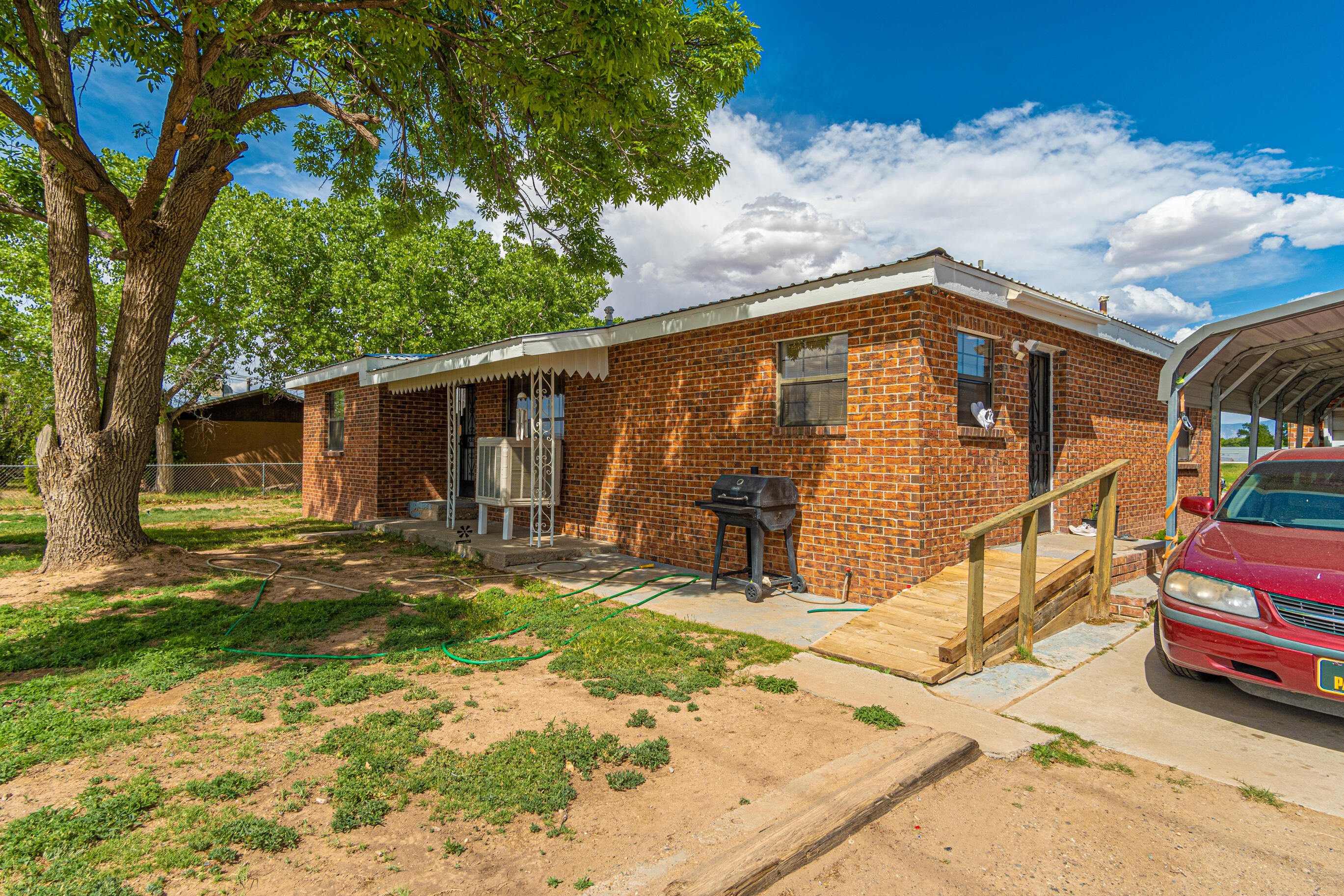 Excellent location with tons of potential & owner will consider Financing!! Come check out this cute home sitting on half an acre.  Three bedroom home with an enclosed patio with an additional 952 Sqft.   Two car garage, pipe fencing, metal roof. This home has the potential to be zoned for commercial use!