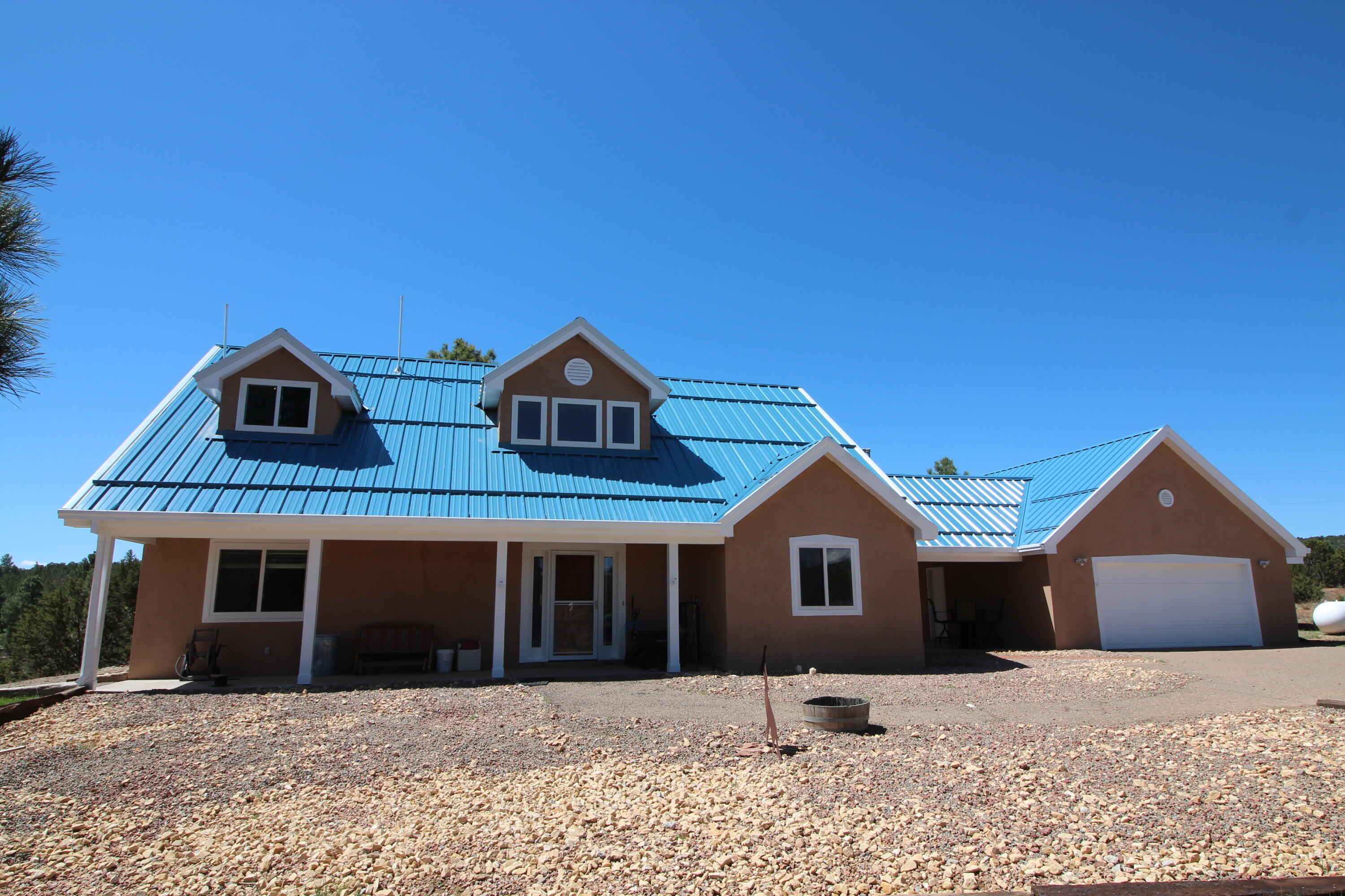 The premier horse property in the East Mountains! 18+ acres of meadow, mature ponderosa pine, views, high producing well, barn, green house, Northern NM custom home, all on a paved drive way! As you pull into this property you are greeted by the peaceful and quiet natural setting of this home. Walk into this updated home with a private master suite with a personal deck to walk out on. Master suite has custom barn doors and a custom shower set up. Downstairs boasts 2 bedrooms, an office, gourmet IKEA kitchen, a grand living room, and a heated converted sunroom with a hot tub and open access to the backyard.  There is a custom green house on the property too! The barn has 3 run outs, 2 concrete tack rooms, and a finished game room! Fully fenced and fenced pasture for any animal you may want.