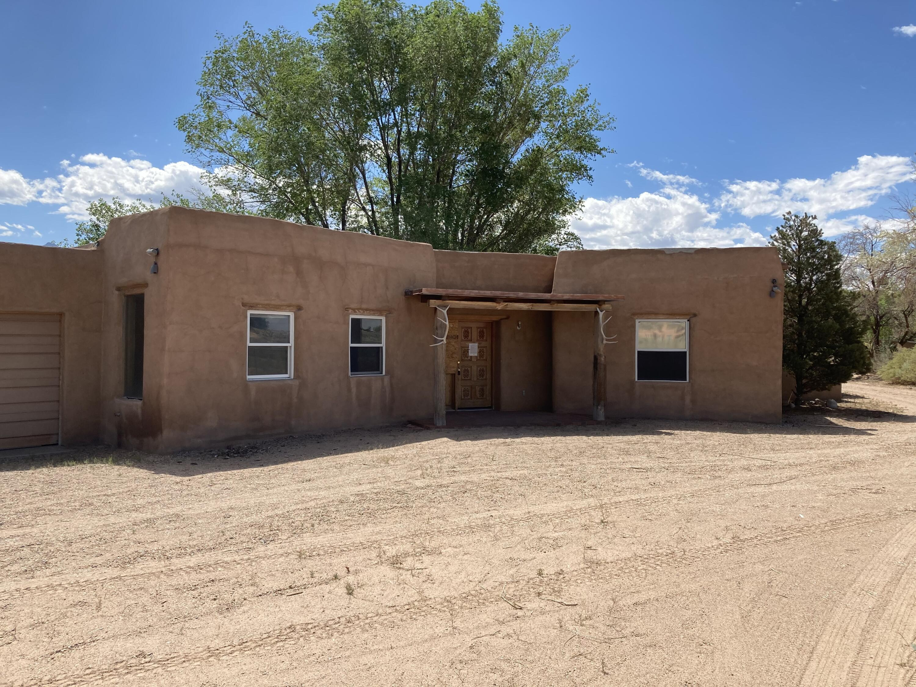 Beautiful custom home in Corrales. Needs TLC but has lots of potential! Kiva Fireplace, large fenced backyard with mountain views. Property will be sold as is.
