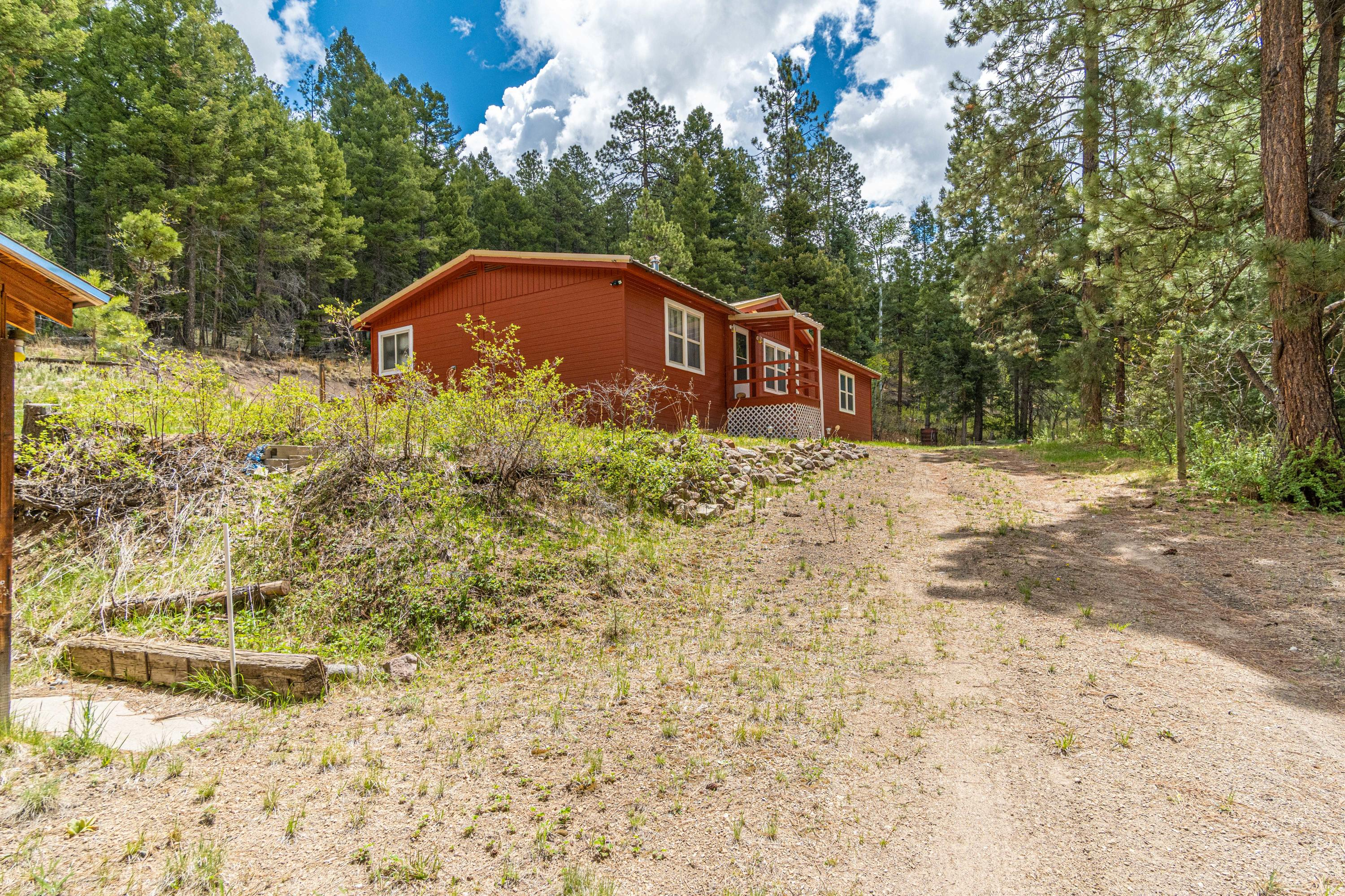 Inspections in hand and ready to sell! Enjoy room inside and out in this 1600+ sq.ft. home on almost 2.5 acres in the Sierra Los Pinos subdivision of the serene Jemez Mountains. Three bedrooms, two bathrooms, well-maintained interior, w/ both a pellet and wood-burning stoves. Multiple cosmetic updates inside & out in last 4 years including  fresh paint on the exterior of the home, new front porch, & new steps in back. Property also boasts a large garage for storing all the equipment, toys, & tools you need to enjoy your new mountain home. Approx. 45 min. from both Los Alamos & US 550 and only 15 minutes from the Valles Caldera National Preserve. NEW furnace 2020 and recently repaired/cleaned ductwork. This home awaits a new owner to love and enjoy it- schedule your private showing today!