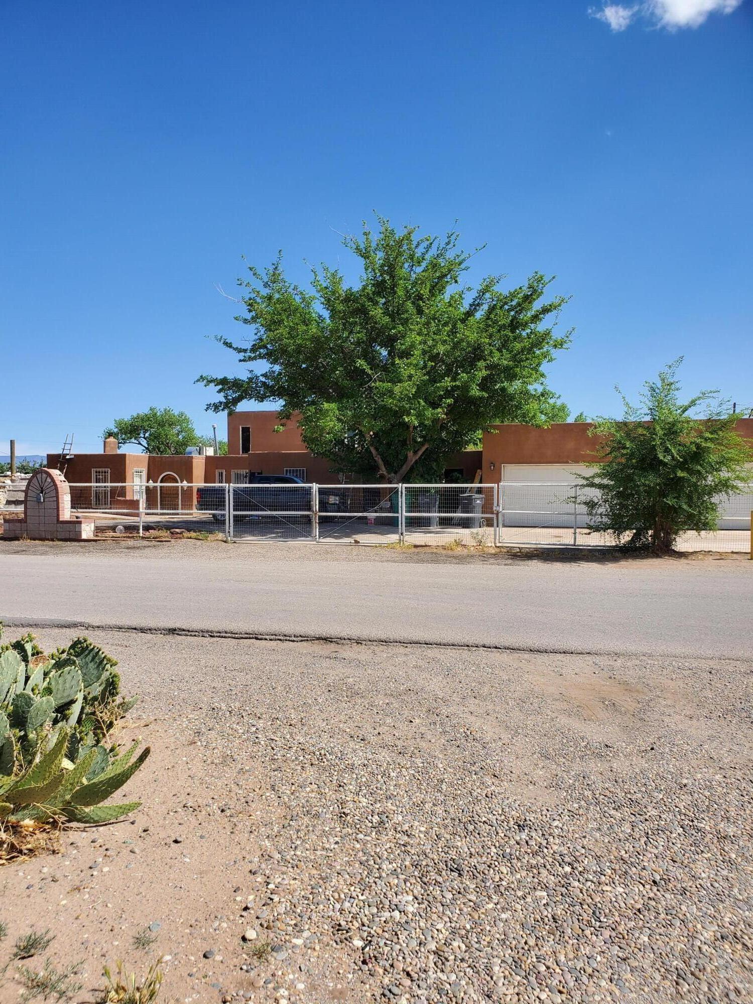 Tons of potential! Custom pueblo style home sitting on an acre, corner lot includes 4 12x11 covered horse stalls and 40x20 storage/utility building, outdoor heated swimming pool with retractable enclosure, outdoor seating area and a loft over the dining/ living area. Plenty of room for a garden plus  camper/trailer parking and horses.