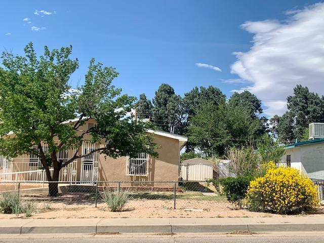 Charming house with large yard near CNM and UNM. House was renovated in 1995. Great location. Huge yard and you may be able to expand with City approval. Kitchen has good cabinets and a pantry. This comes with a gas range and side by side refrigerator. Tile flooring in kitchen, dining room, bathroom and laundry. Laundry area off of hallway. 2 coat closets for extra storage. Bathroom has linen closet. House has metal wrought iron on windows and nice ramp to front door. There is a porch in the backyard and two storage buildings. Backs up to UNM recreational and stadium centers.