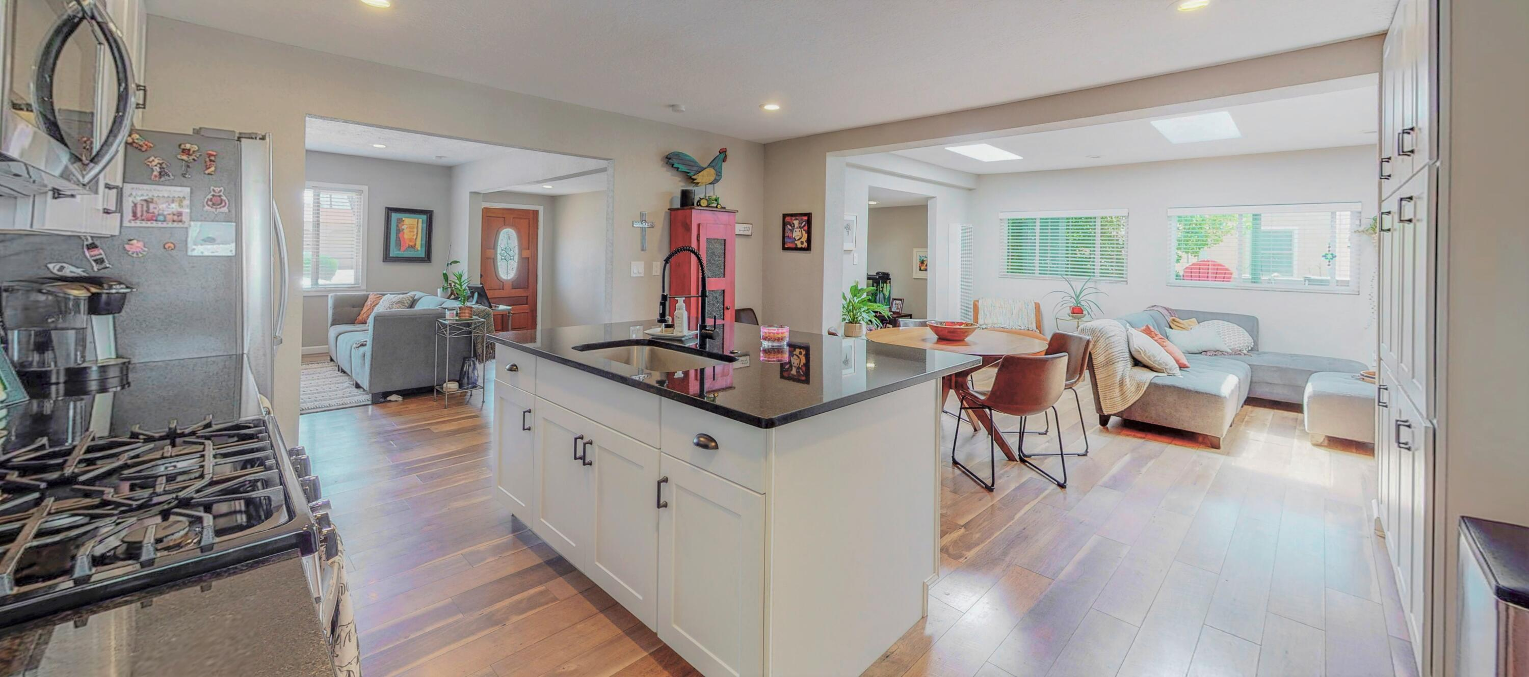BEAUTIFUL open concept home in UNM/Ridgecrest area. Large modern kitchen with oversized center island and custom granite, plus high-end stainless appliances. Two spacious living areas including a great room with skylights for entertaining studying or relaxing. Spa-like custom bathrooms with floor to ceiling tile and modern cabinetry.  Includes 250 sq ft fully heated and cooled backyard gym/studio just across the large custom built deck. Master BR has it's own wood burning fireplace plus Enormous one-of-a-kind ''walk around closet'' (with two entrances). Gorgeously landscaped, the lush and shady backyard oasis has a huge shade tree as well as an established producing cherry tree. Bandolier school district! Easy freeway access and close to labs, Facebook, Mesa Del Sol & TWO universities.