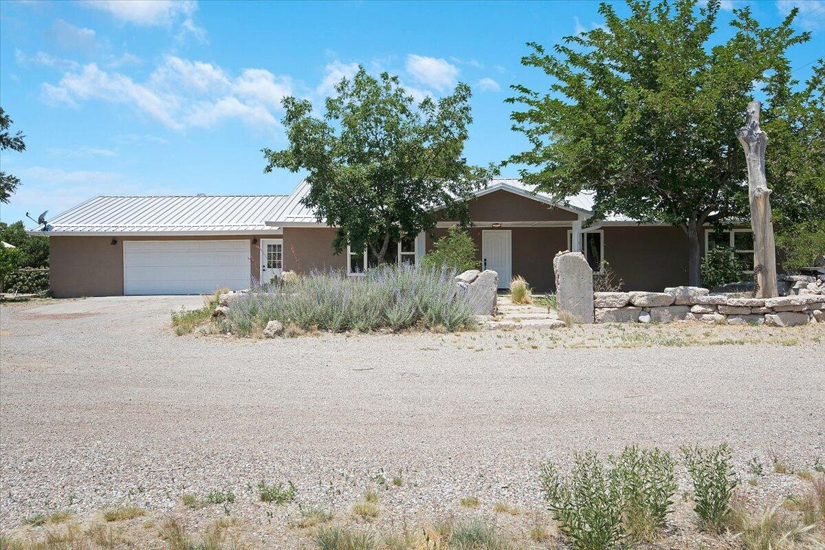This home in the foothills is the perfect mix of nature and near, with big sky views and room to roam just 10 plus minutes to the big I.  Enjoy the shade of mature oaks and evergreens, and the beauty of all things blooming on this 1.5 acre estate bordering the Tjeras arroyo and wildlife corridor.  This 3 bed, 2 bath 2400 sf ranch-style home has been totally renovated with concrete countertops in the open kitchen and new stainless steel appliances, redone bathrooms, new doors and hardware and a mix of luxury vinyl and ceramic tile floors.  There's also a new mini-split heating and cooling system with five separate zones for personalized comfort year round and a wood-burning stove that really cranks out the heat!  There's new synthetic stucco on the outside, a new pro-panel roof and new seam