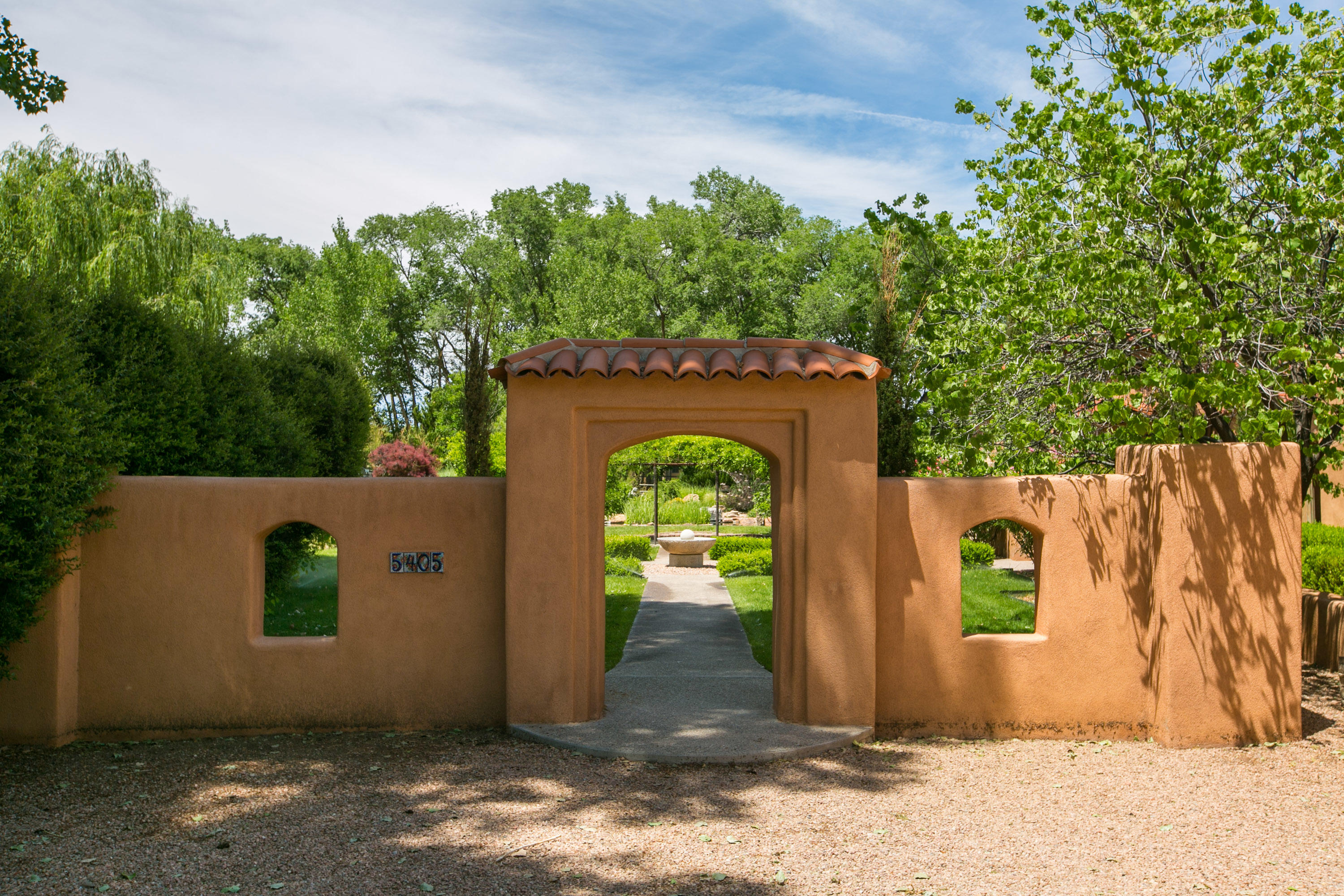 Spectacular hacienda-style home on a breathtakingly manicured lot off Rio Grande. John Calvin adobe, situated on an acre with mature trees, numerous courtyards, and plenty of privacy. Enter through the resort-style courtyard to a formal living room overlooking the garden and the koi pond. Boasting both a formal dining and a cozy eat-in with kiva fireplaces. Carefully thought-out floor plan with master on north wing and other bedrooms to the south. Kitchen features include: Wolf range, subzero fridge, double-oven, wine cooler, & oversized island. Views of landscaping can be enjoyed through every window in the house. Walled back yard has an ideal location for a pool. Three car garage, radiant heat, travertine tile, & so much more. Call for your private showing.