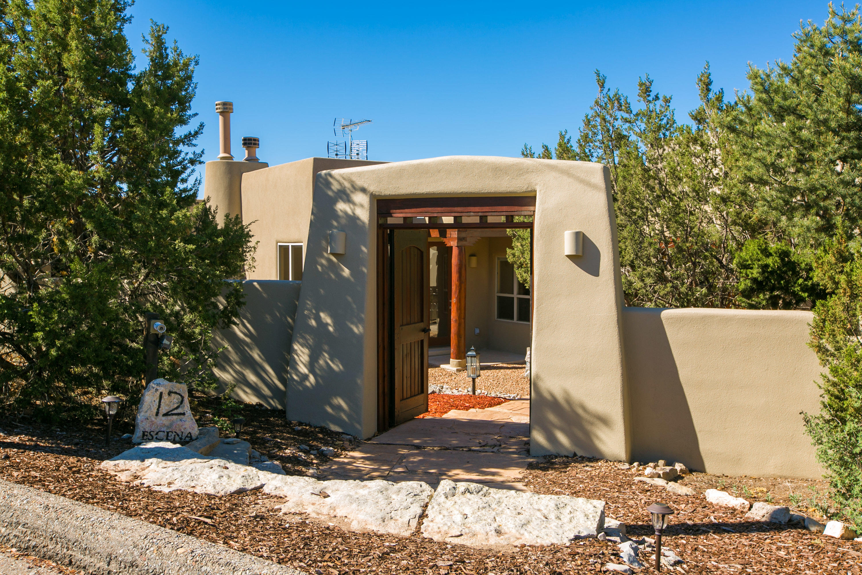Custom built home is situated on a scenically supreme location with frameable views from most of the living areas of the Sandia & Manzano Mountains & the Tijeras Canyon, spectacularly showing the beauty and splendor of all that New Mexico has to offer. Enter this beautiful 4 bedroom, 3 bath, custom home through the private courtyard where you can enjoy the soothing sounds of the waterfall pond or a glass of wine next to the outdoor fireplace.  A large foyer & bright living room cheerfully welcomes any visitor into this elegant home that boasts pride of ownership.  Custom features such as diamond plaster gas kiva fireplaces (3), tongue and grove ceilings and vigas provide a dash of southwest flair.  Fully tiled flooring & radiant heat help those with allergies & pet