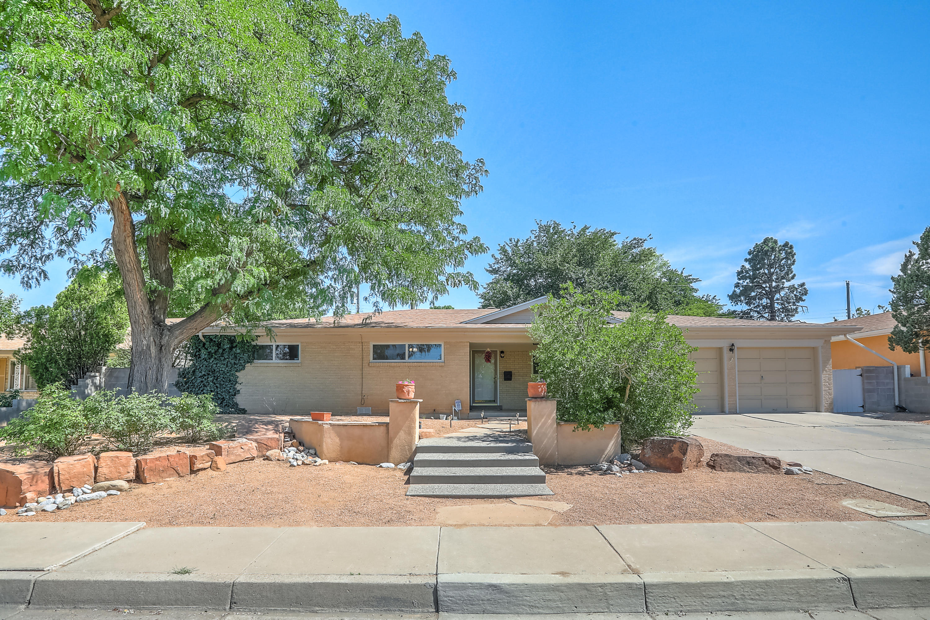 An truly exquisite, rare find in the UNM area. Prime location. Magnificently updated and cared for. Desirable, brick, single story floorplan boasting a modern renovated eat-in kitchen. Incredible natural lighting. Easy maintenance tile flooring throughout the high traffic areas. Two living areas. One featuring warm and inviting wood floors, built-ins, wood burning fireplace, and wet bar. Spacious bedrooms with new carpet. Large covered patio. Fully landscaped backyard retreat with mature trees and lush grass. One year old roof. Refrigerated A/C. Arguably one of the best locations in town. Situated in the heart of the city, tucked away in the tranquility of Netherwood Park. An absolute gem.