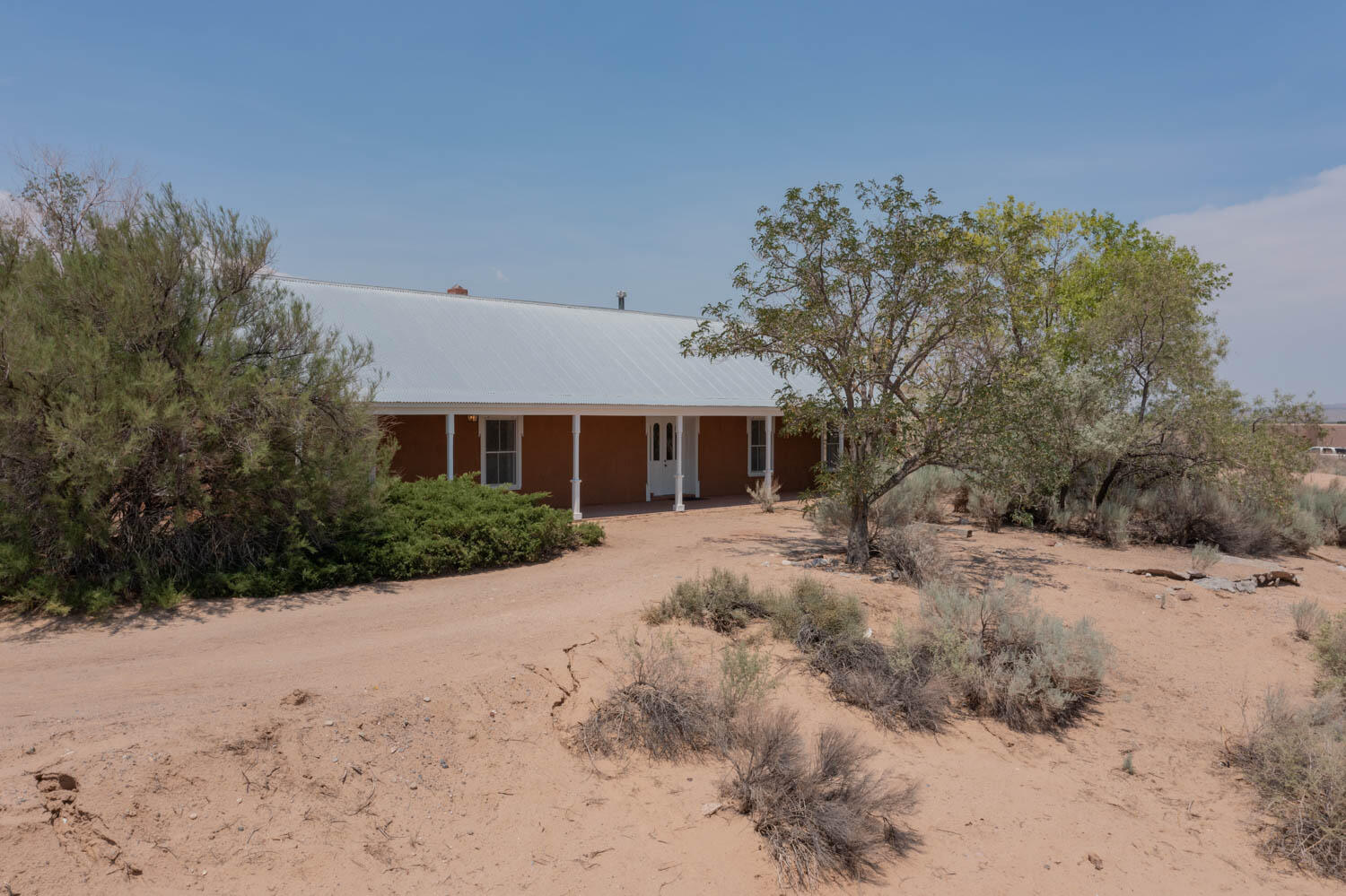 PRICE REDUCED!   Don't miss the breathtaking views from this gorgeous unique Northern New Mexico style home built by Corrales builder Pete Smith.  This adobe home is nestled on 3.5 acres at the end of a private road.  Enjoy beautiful brick floors, huge bedrooms, 3 Kiva fireplaces, and a front portal that runs the length of the home on which to sit and take in the incredible views.  So much charm and plenty of privacy.Please note that most everything in this home is original, which adds to the charm, however, a buyer may wish to update. One of the furnaces was replaced within the last year or so, along with the well pump. New stucco and new storage room roof in 2021.  Septic tank replaced Aug 2021.