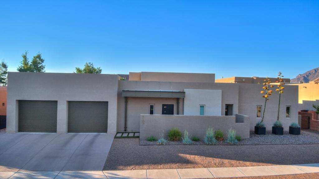 Modern, contemporary, custom 3-BR, 3-BA home in a small, gated community in NE Albuquerque. Friendly neighbors, easy upkeep, energy efficient and excellent security make this a unique opportunity. The back patio provides a private, quiet area for that morning cup of coffee. Enhance the experience with music from built-in speakers and the ambiance of a lovely garden area. The large quartz island in the gourmet kitchen makes entertaining a joy. Top-end appliances (48'' SubZero refrigerator, Wolf stovetop, oven and microwave, and Miele dishwasher) make meal preparation a breeze.  The oversized 2-car garage includes an additional tandem work space perfect for weekend projects. The xeriscape landscaping has a fully integrated drip system coupled with synthetic grass make upkeep minimal.
