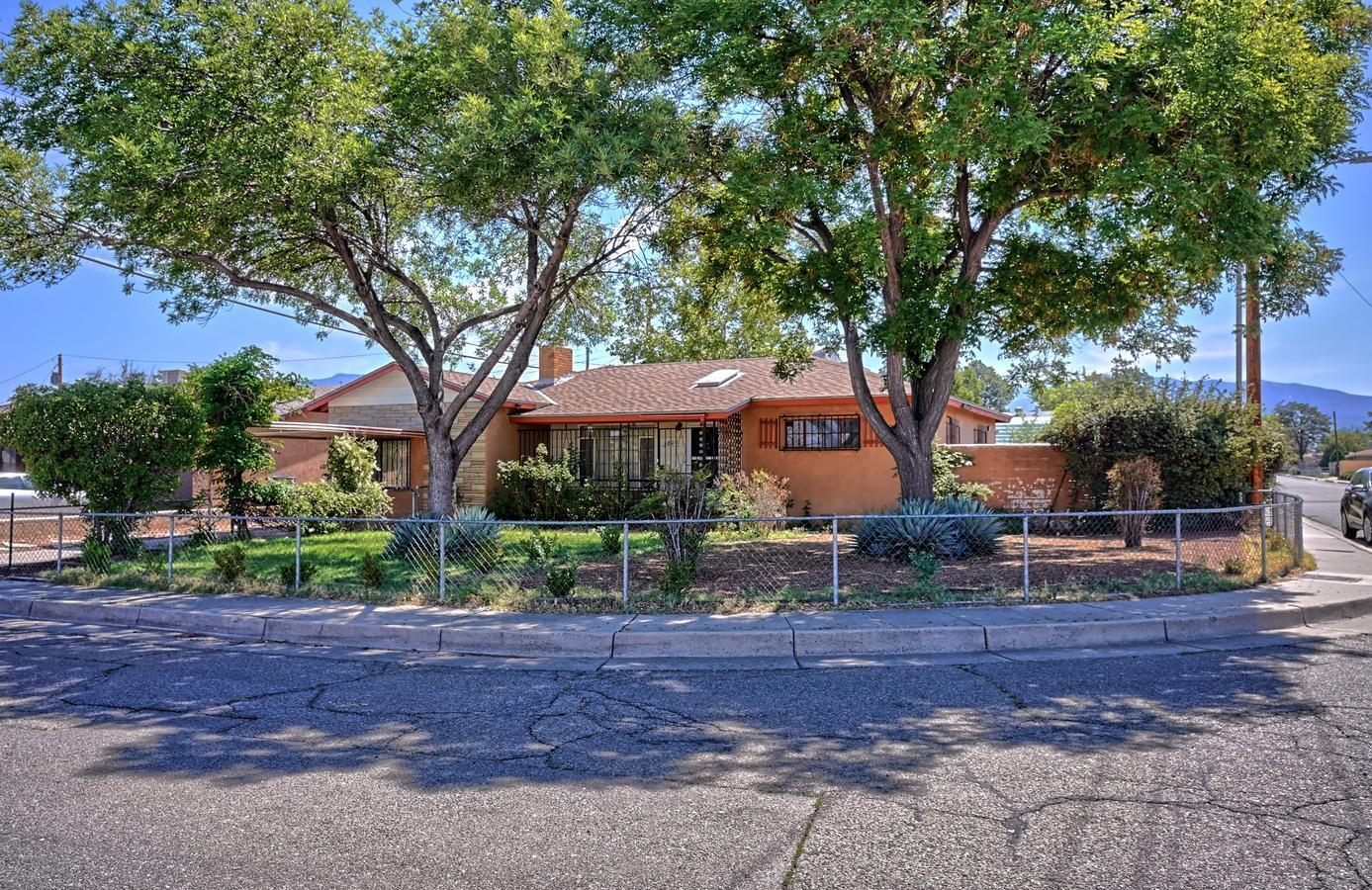 This charming home features original hard wood flooring, a wood burning fireplace, two recently replaced evaporative coolers, and a bonus living area.  The oversize lot features mature rose bushes large shade trees and grass. Centrally located home near malls, dining, health care and recreations. Two minute drive to Interstate 40.  Sewer line replaced in 2015. Recently stuccoed.