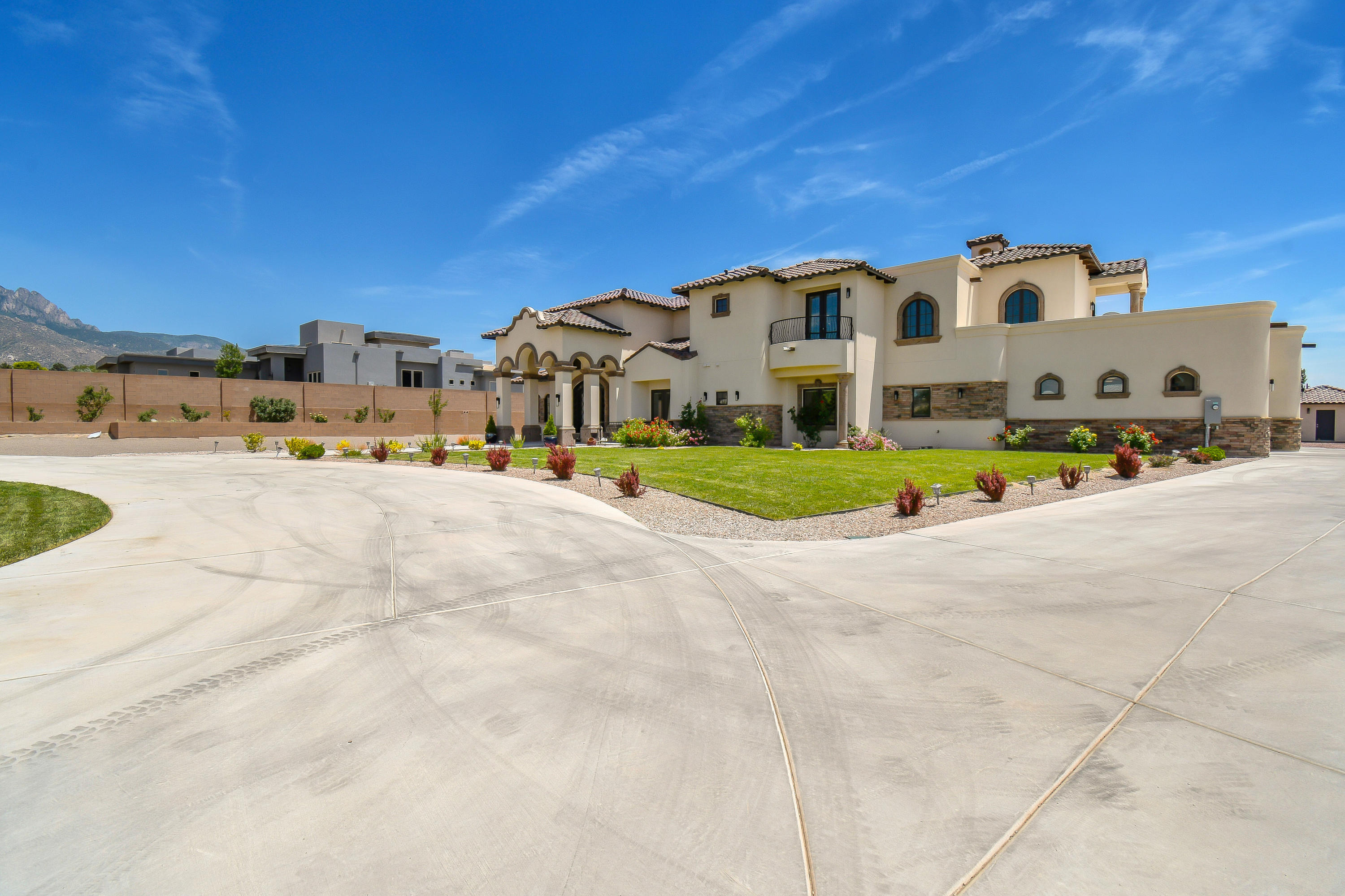 This pristine home blends Tuscan-style architecture with contemporary interior design. Designed and built without compromises, it sits in the shadow of the Sandia Mountains in one of Albuquerque's most desirable locations. From the sun-splashed grand foyer to the 5 ensuite bedrooms with balconies, the home is filled with light - accentuated by artistic fixtures throughout. A modern chef's kitchen is bold and beautiful, while the state-of-the-art media room and wet bar are perfect for relaxing. Space abounds, with generous walk-ins and a 4-car garage. Entertaining? The huge covered patio includes an outdoor kitchen, and the pump house is ready for a pool! For families that love life both indoors and out, this unique home is both your sanctuary and your gateway to the New Mexico lifestyle.