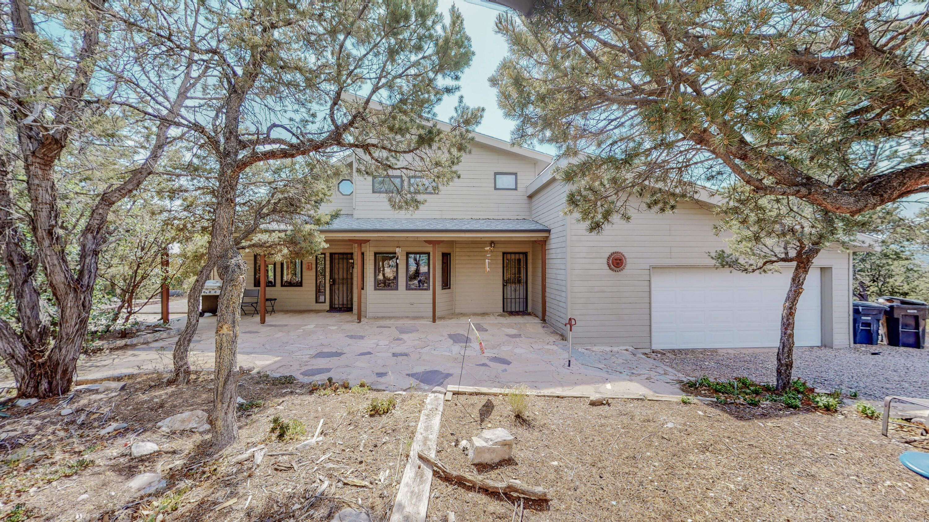 Welcome home to this beauty in the woods!  Gleaming brick floors throughout the lower level invite you to cozy up & enjoy the views from all the wood clad windows! Let the large wood stove keep you toasty in the winter. This 3 bedroom 2 1/2 bath with oversized garage & extra hobby room or office is just what you need to be close enough to Albuquerque but far enough away to feel like it's a sanctuary!  Situated on almost an acre, you have privacy yet still have the feel of a neighborhood.  Enjoy the beautiful views & quite!  Luxury living at affordable pricing!  Come put your special touch to this home in the woods!