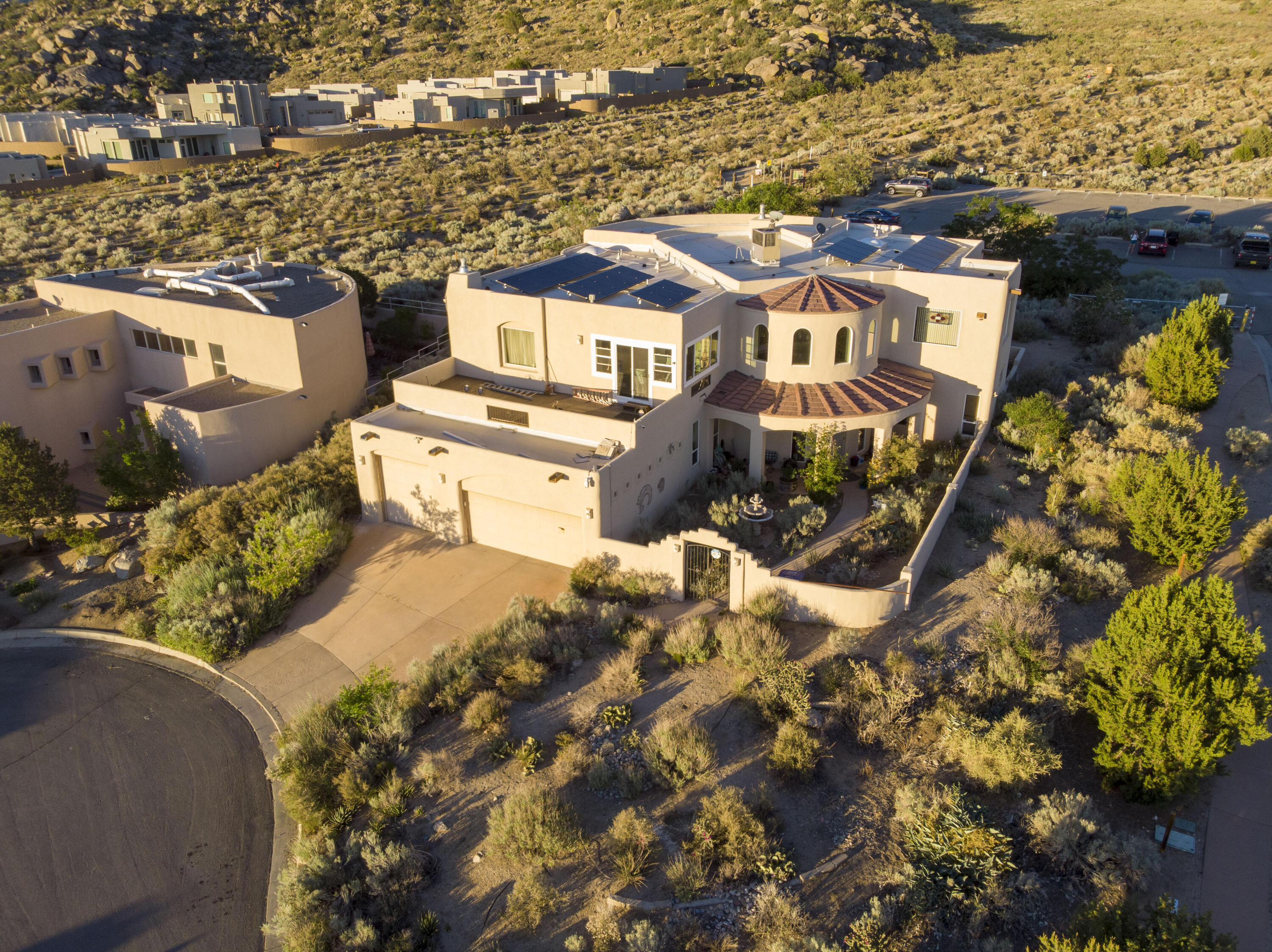 Rare opportunity to own a custom-built luxury home, just steps from the Embudito Trail and the foothills trails system - in the desirable community of High Desert.  This home features almost 900 square feet of balconies so that the incredible views of the Sandia mountains and the city lights can be enjoyed to their maximum potential.  Few properties in the city combine the natural beauty of the foothills and convenience of nearby shops and restaurants.  This nearly 5000 square foot home features six bedrooms, five bathrooms, a large finished basement, paid for solar panels, and an elevator.  This home has also been recently updated with a new roof, 3 new refrigerated air units, and complete re-stucco (all in 2018).