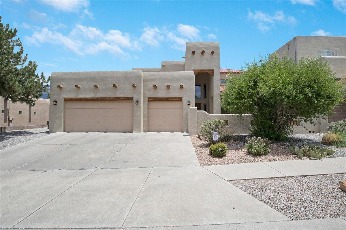 Former Raylee Homes model in Quintessence with Sandia mountain views! Backyard Oasis, private, custom pool, waterfall, newer deck, covered patios, hot tub, basketball area, grass, trees & fireplace! Welcome guests into your private courtyard, covered porch & French door access to living room & dining with custom built in cabinet. Newer Hardwood floors downstairs. Eat-in Kitchen boasts island with sink, wine rack, oversized pantry with built-ins, gas range, built-in wall oven & microwave. Family Room, raised custom wood ceiling, gas log kiva fireplace, recessed lighting. Downstairs master, custom ceiling, 2-way fireplace, walk-in closet, double sinks, jetted tub, separate shower. 3 upstairs bedrooms plus walk-out to roof top deck with Sandia views! Custom wood doors throughout. Newer Stucco